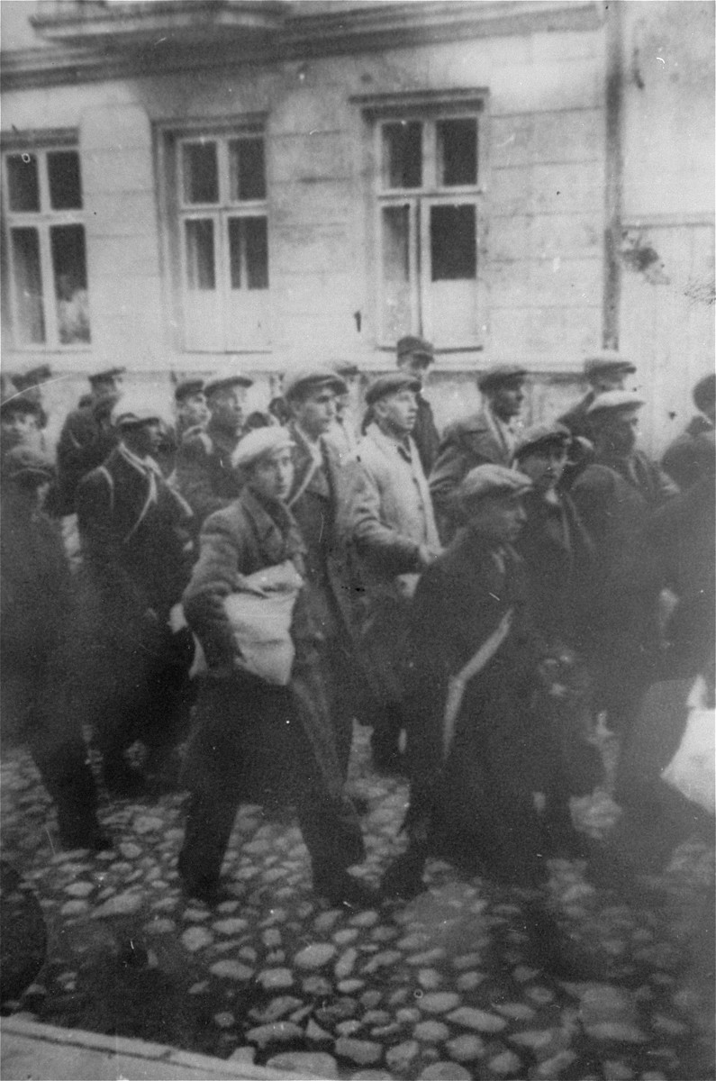 During a deportation action in the Brzeziny ghetto, Jews are marched through town to the railroad station in Galkowek.