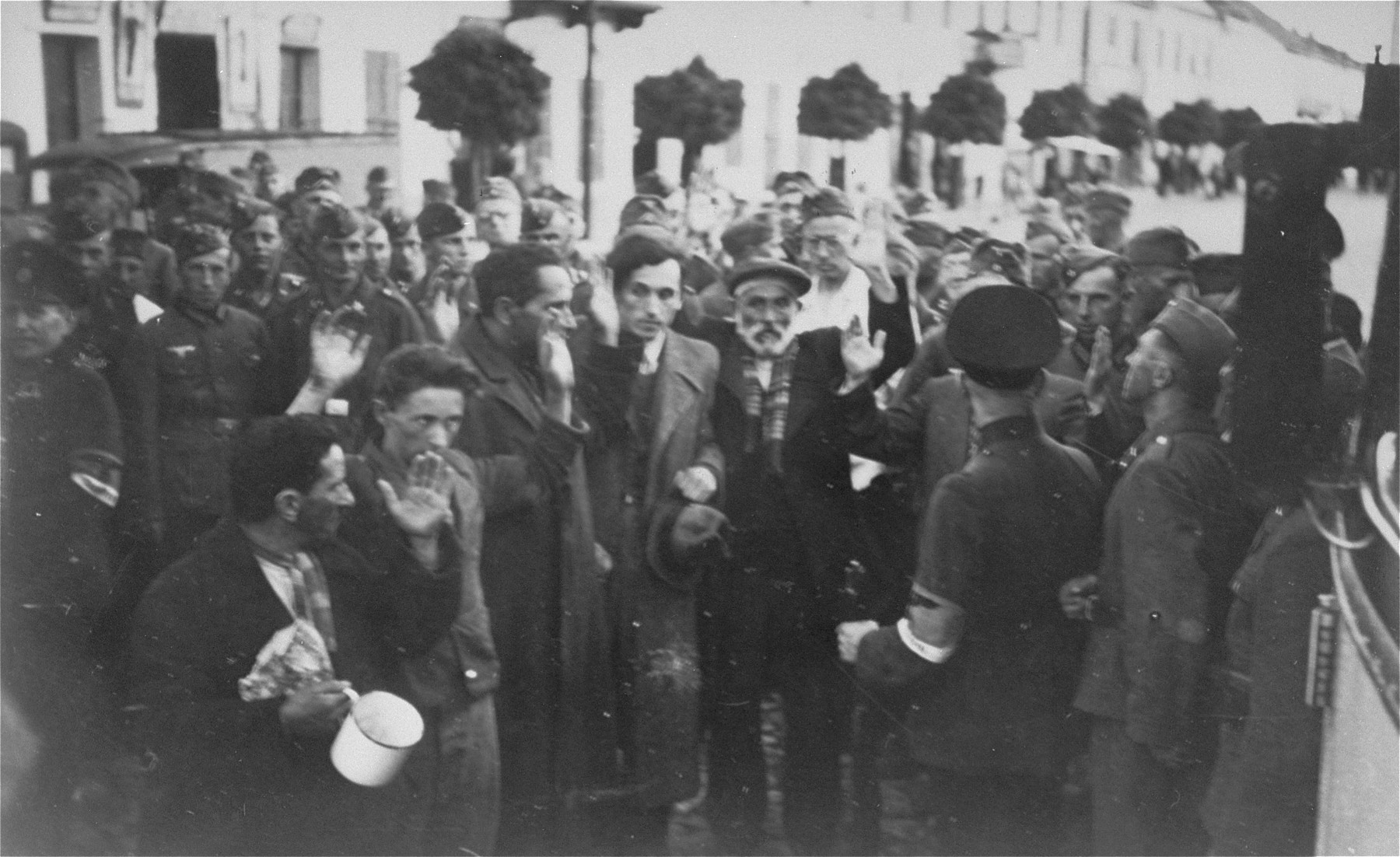 German soldiers surround a group of Jewish men who stand with their hands up in a public square in Bialystok.