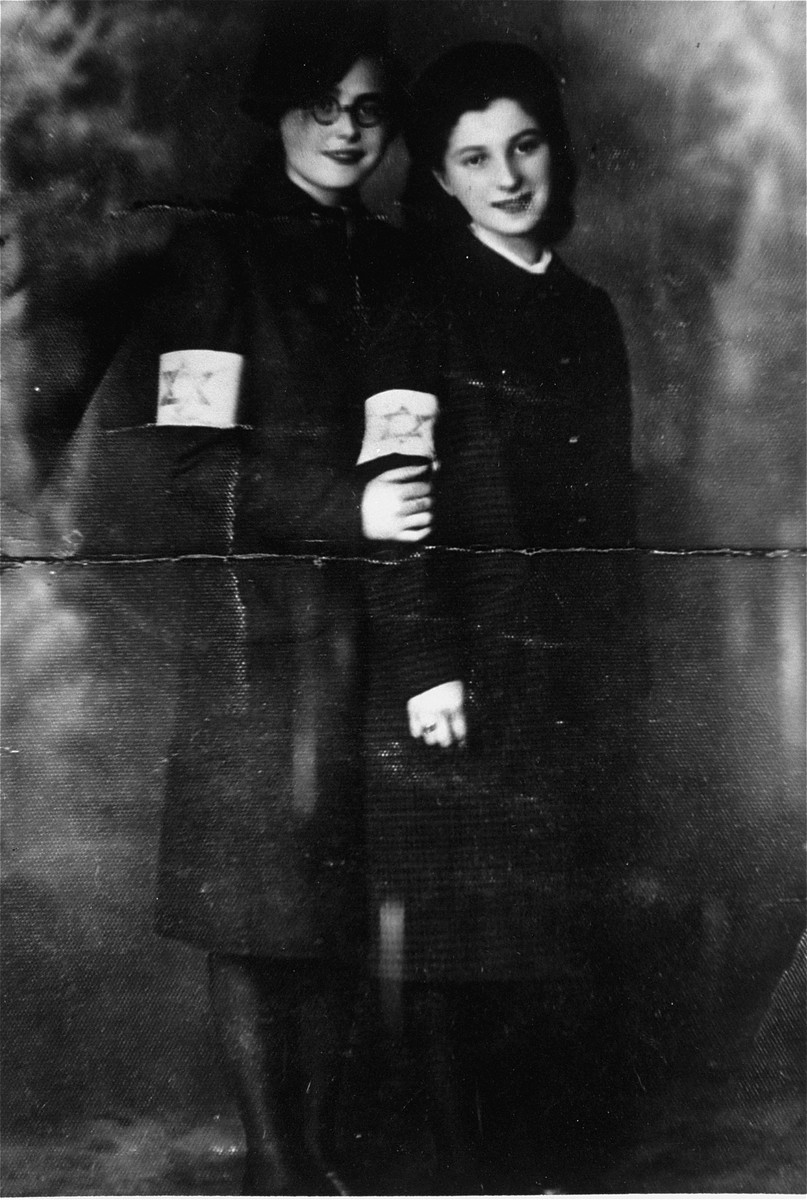Two female cousins pose wearing armbands in the Czestochowa ghetto.  Pictured are Mania Leszczyk (right) and her cousin, Cela Dauman (left), both of whom survived the war.