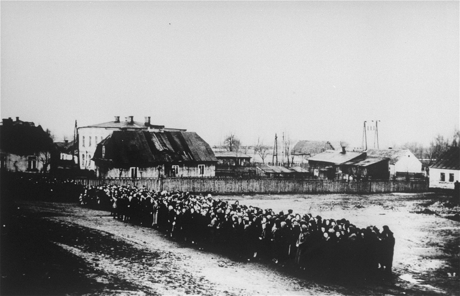 View of a column of Jews lined up along a road during a resettlement or deportation action.