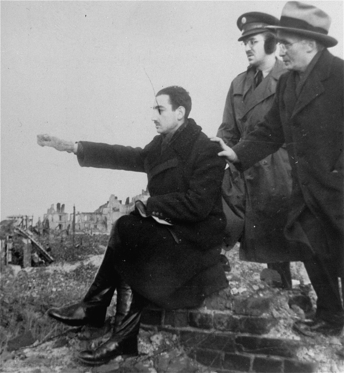 Marek Edelman points out where the Mila 18 bunker was among the ruins of the Warsaw ghetto.  Behind him stands Jacob Patt, a delegate of the American Jewish Labor Committee (formerly of Bialystok).