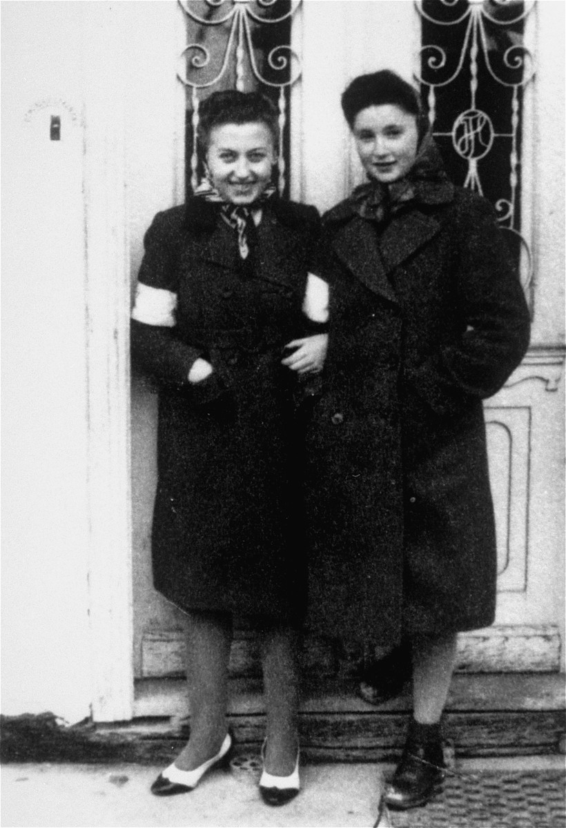 Two young Jewish women pose wearing armbands in front of the Fleischer home in the Borislaw ghetto.  Pictured are Nina Fleischer and Fania Begleiter. Fania perished during the war.