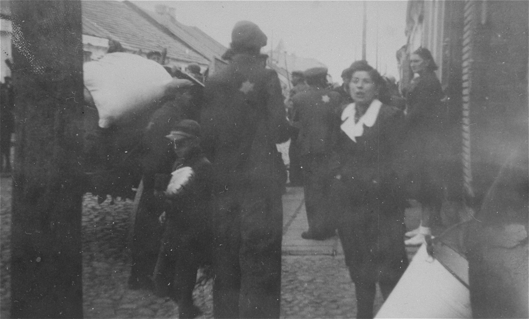 Jews stand on Pabianicka Street in Belchatow during a resettlement or deportation action.