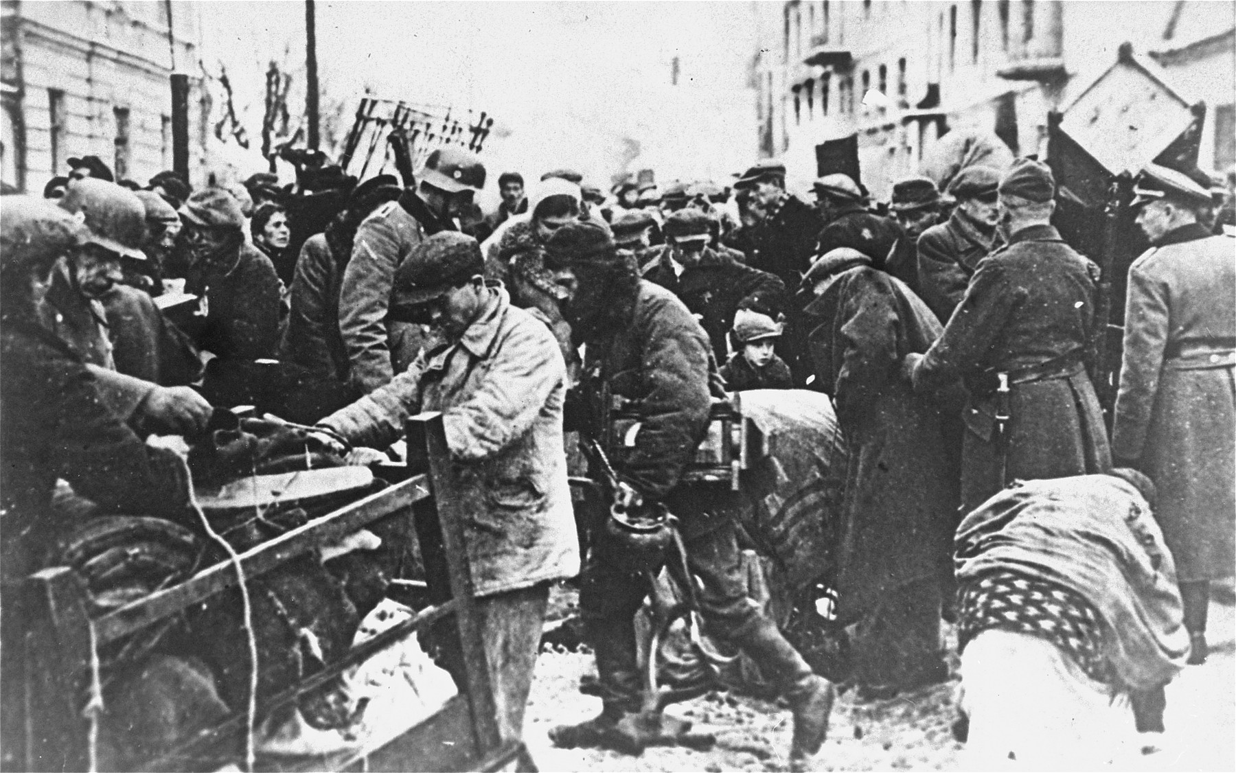 Under police supervision, Jews move their belongings into the Grodno ghetto.