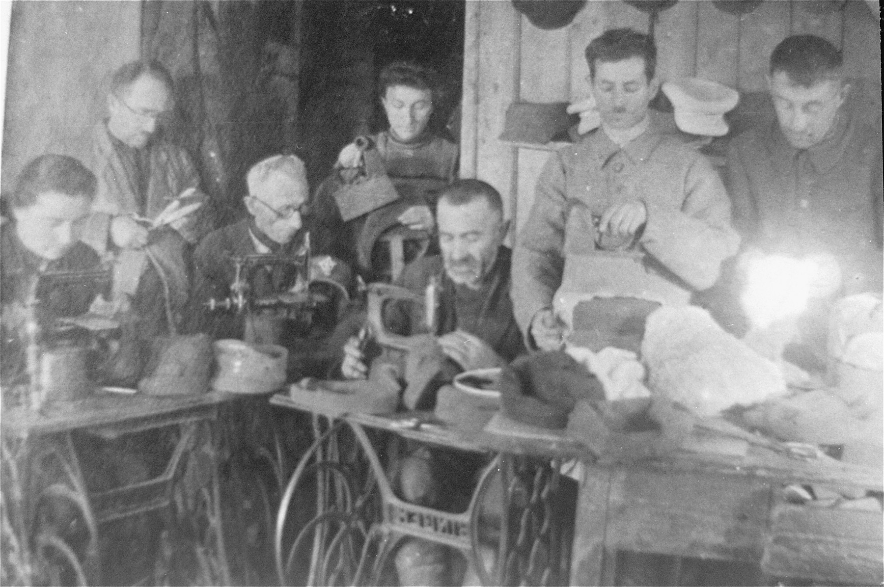 Jews sewing military hats in a workshop in the Glubokoye ghetto.