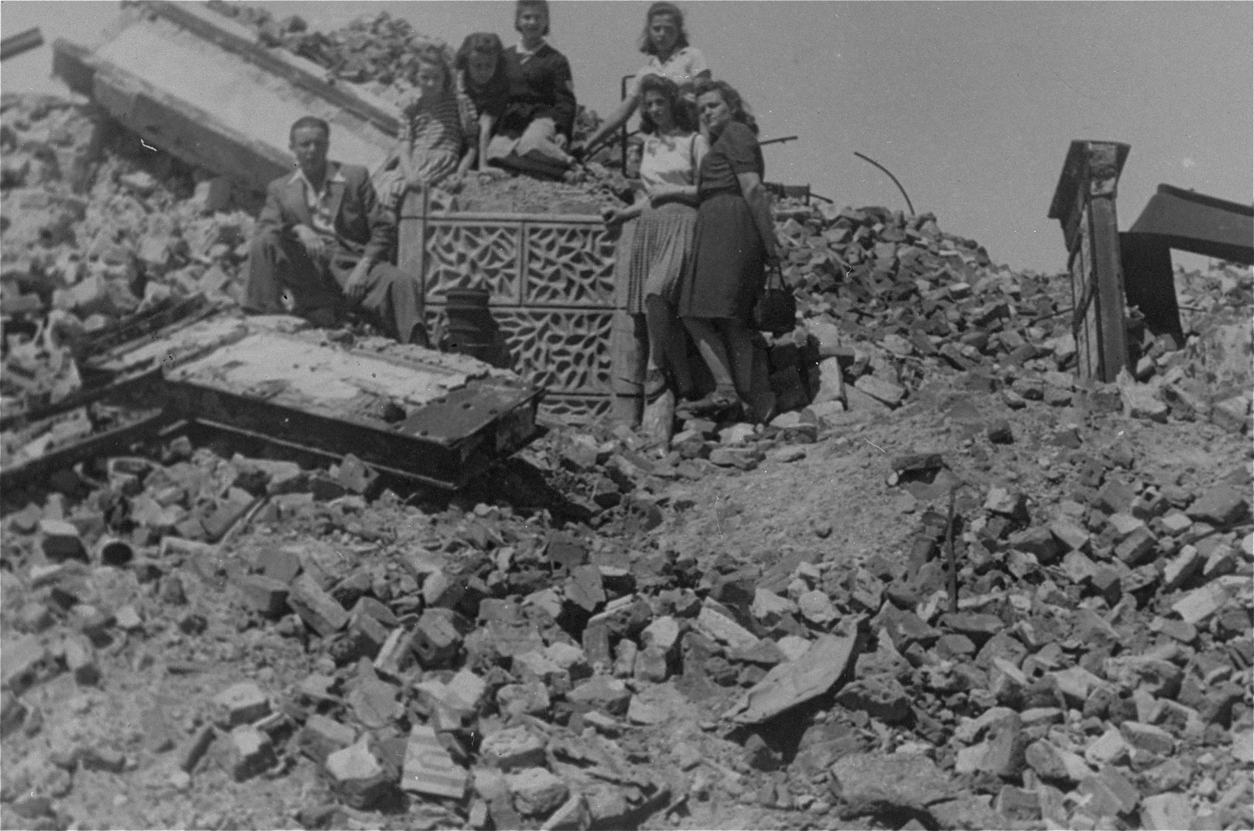 Survivors of the Jewish underground pose atop the ruins of the Mila 18 bunker in the former ghetto.  Among those pictured are Lodzia Hamersztajn (second from the right) and Szymon Rathajzer (later Simcha Rotem) (left).  Both were members of the Zionist youth movement and the Jewish underground in Poland.   Rathajzer's nom de querre was Kazik.
