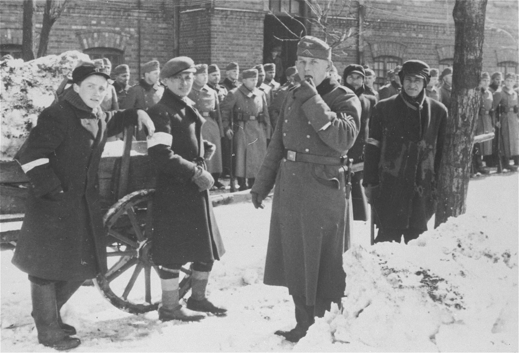 Young Jewish men who have been assigned work clearing snow stand in front of a formation of German troops.  Among those pictured is Leon Celnik (second from the left).