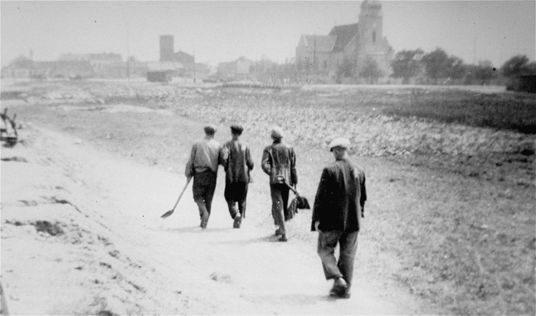 Jewish forced laborers from Belchatow walk along an unpaved road carrying shovels.