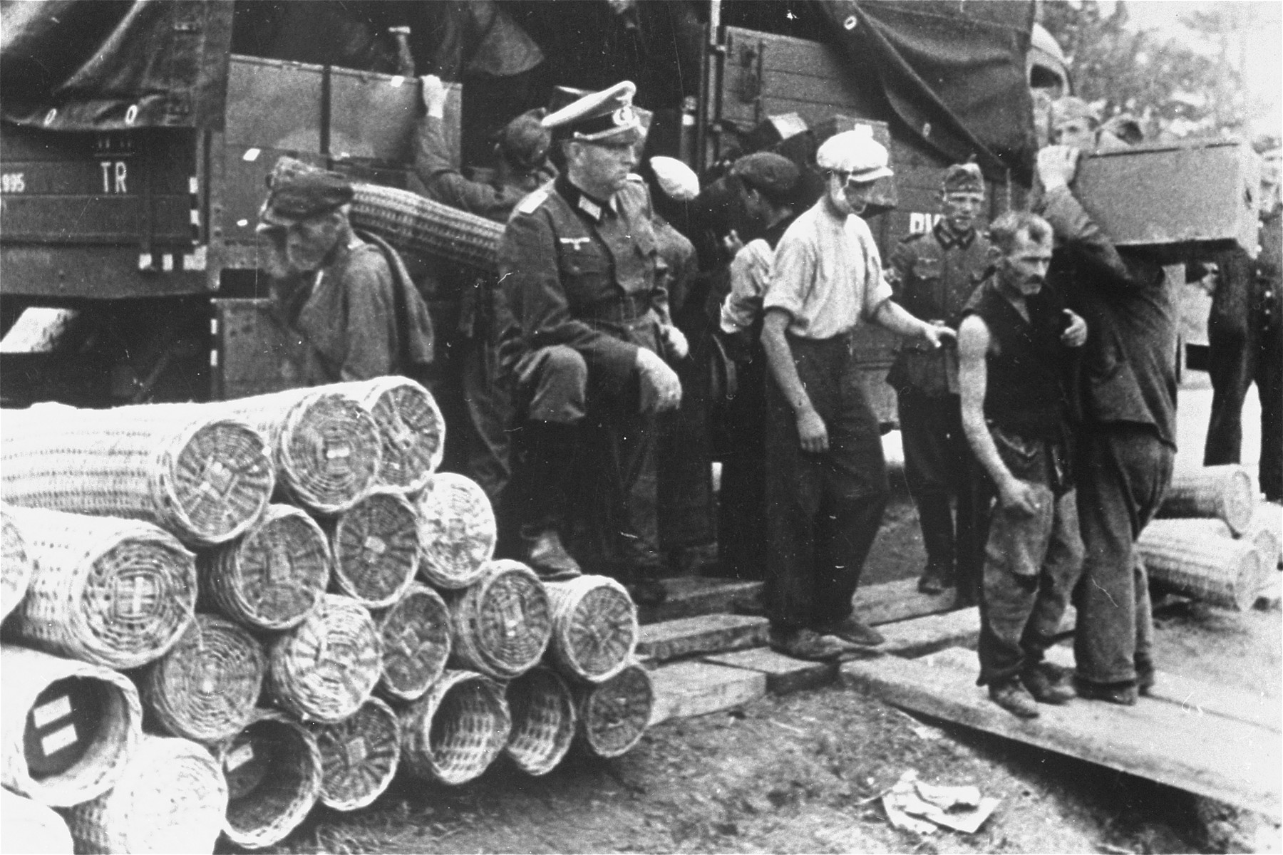 Jewish men are forced to load a munitions train under German supervision.    At the left, a German officer leans on a pile of artillery shells encased in protective woven baskets. [regular and oversized photo]