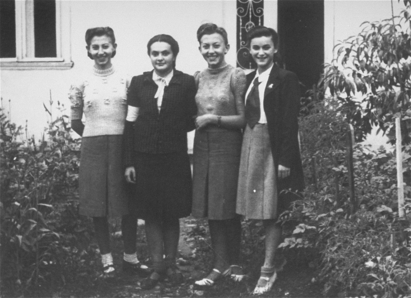 Four young Jewish women pose wearing armbands in front of the home of Renie Scheinberg in the Borislaw ghetto.  Pictured from left to right are: Luka Fleischer, Renie Scheinberg, Nina Fleischer, and Ella (last name unknown. Renie and Ella perished during the war.