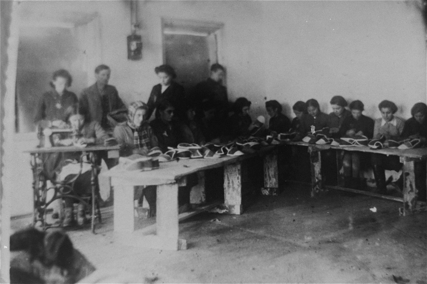 Jewish women at work producing house shoes in the Glubokoye ghetto.