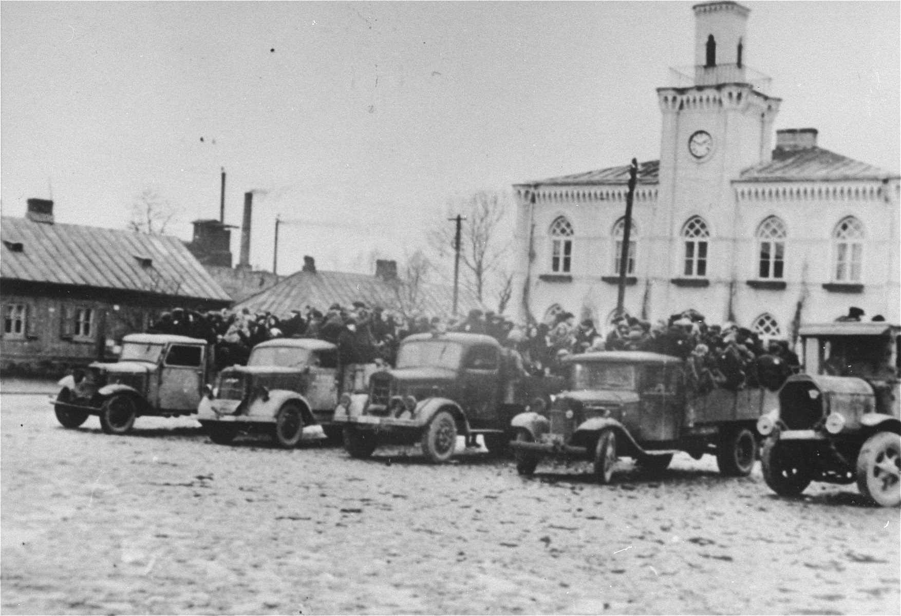 Jews are packed onto a number of trucks that are parked in front of the courthouse and city hall in Marek Square in Ciechanow.