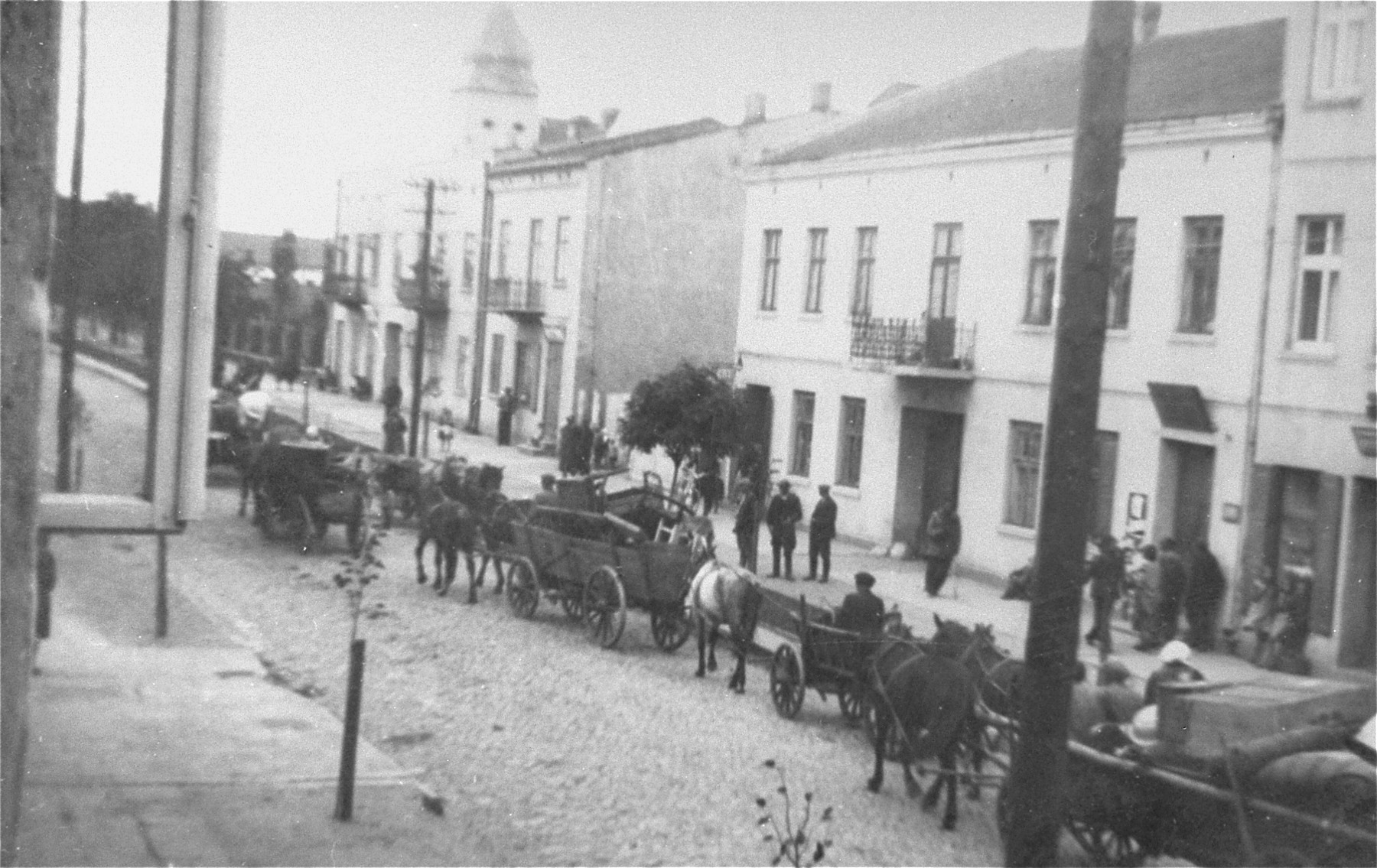 Horse-drawn wagons are lined up along Kosciuszko Street in Belchatow during the relocation of Jews to the ghetto.