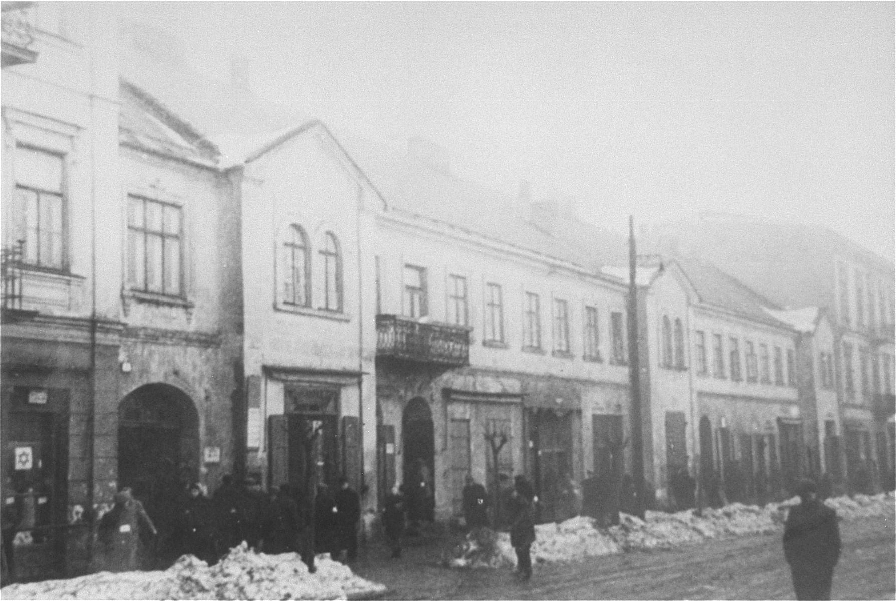 Jews walk along a snow covered commercial street, known as First Aleja Street, in the western part of the Czestochowa ghetto.