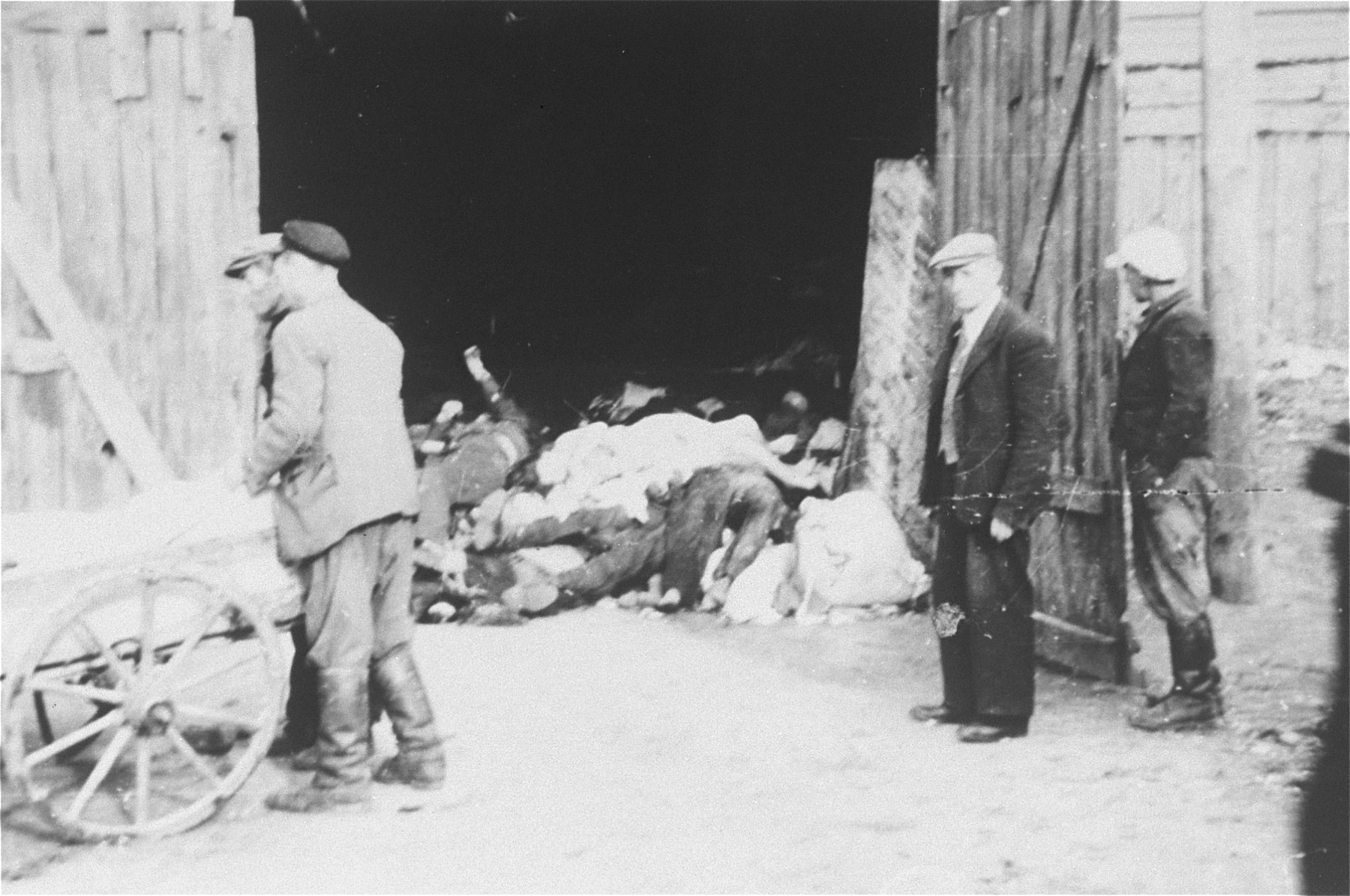 A Jewish council official named Kaminski (right, in front of the door) watches as men remove corpses from a cart and pile them in a barn in the Deblin Irena ghetto.