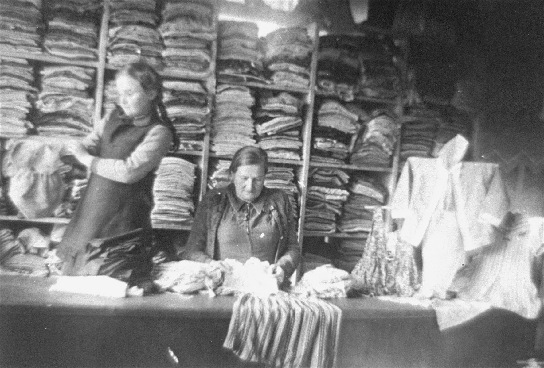 A Jewish woman and girl work in a clothing warehouse in the Glubokoye ghetto.    Among those pictured is Rajze Lederman.