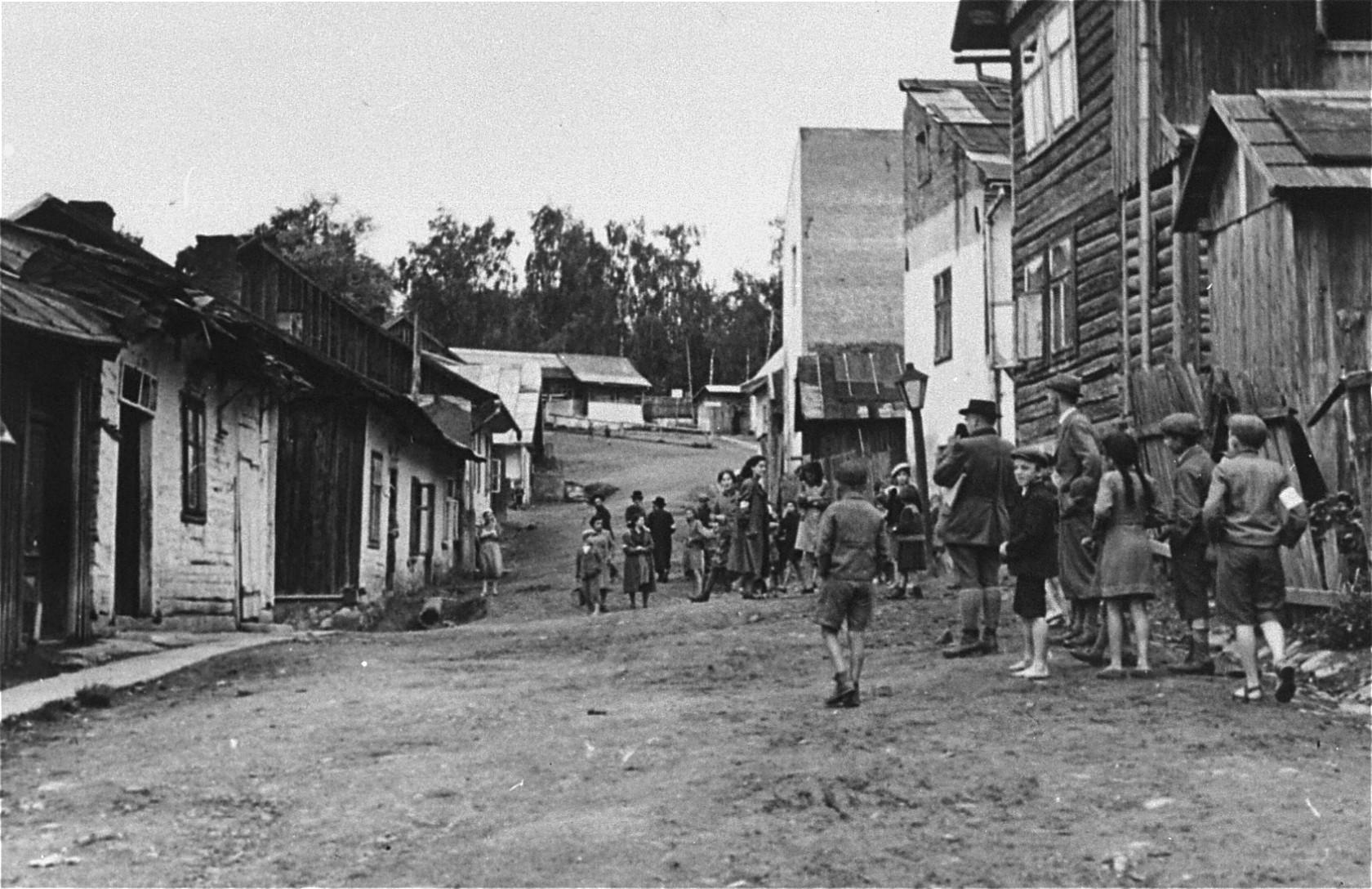 Jewish children walk along an unpaved street in the Frysztak ghetto.