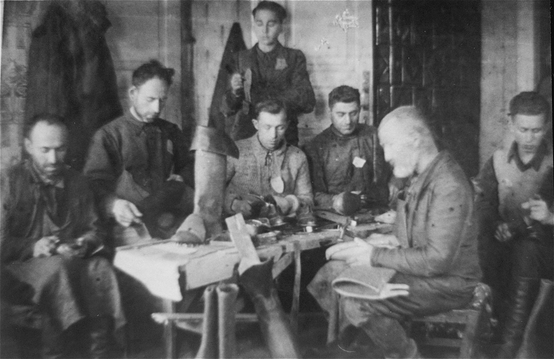 Jewish men at work in a shoemaking workshop in the Glubokoye ghetto.