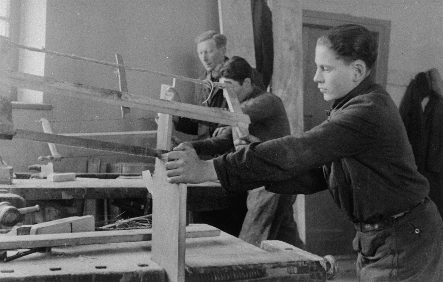 "Jewish youth saw pieces of lumber in a carpentry workshop in the Bochnia ghetto.  The original German caption reads: ""City workshops in Bochnia.  Jewish labor strength made useful.""   Pictured in the foreground is Romek Abraham Marber. The boy with his face covered is Matzner  and the man in back is the workshop manager, Ginsberg or Greenberg.  He was an architect from Krakow."