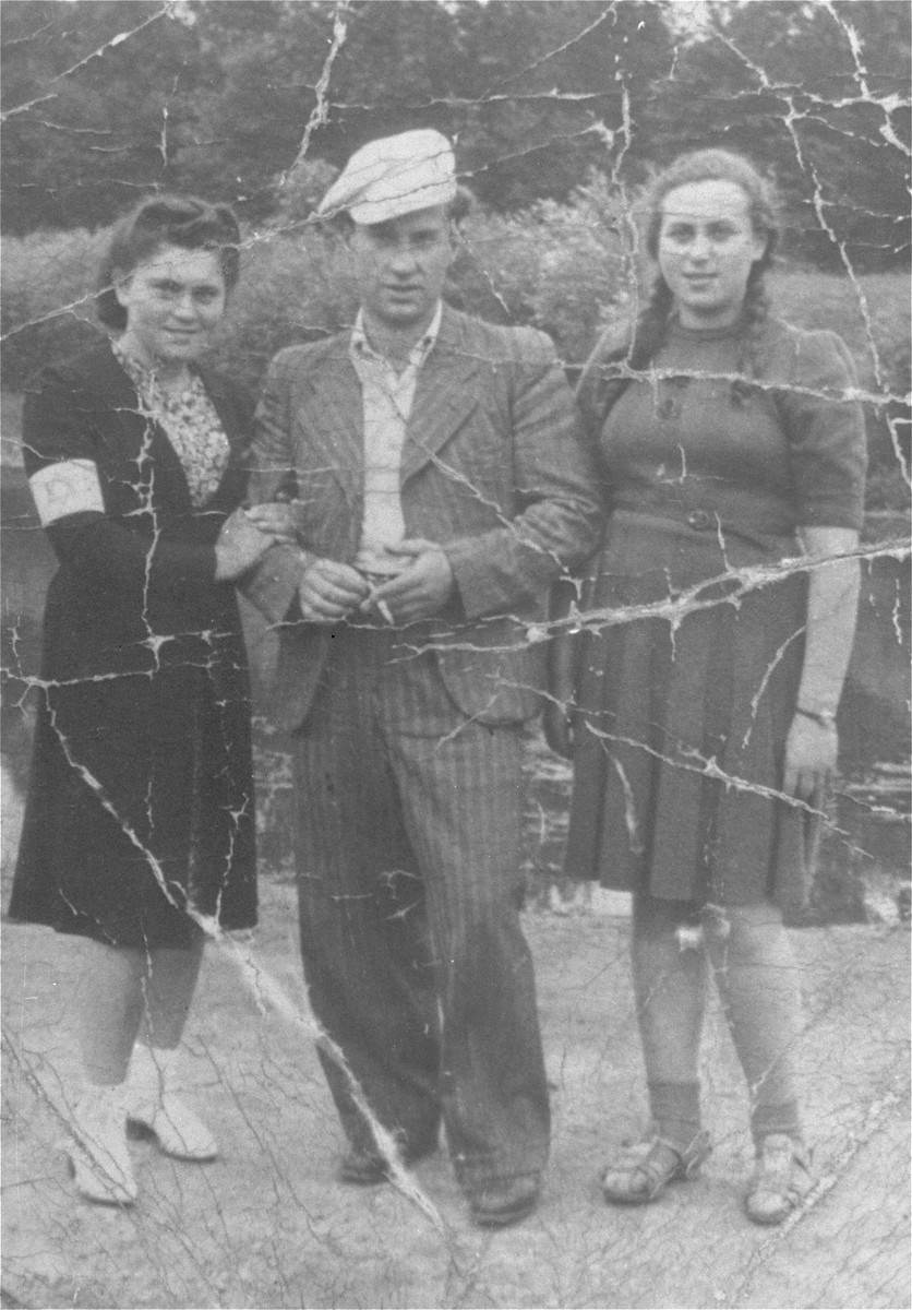 A young man poses with two young women in the Czestochowa ghetto.  Pictured from left to right are Hela Kornberg, Jack Shipper and Hela Munowicz.