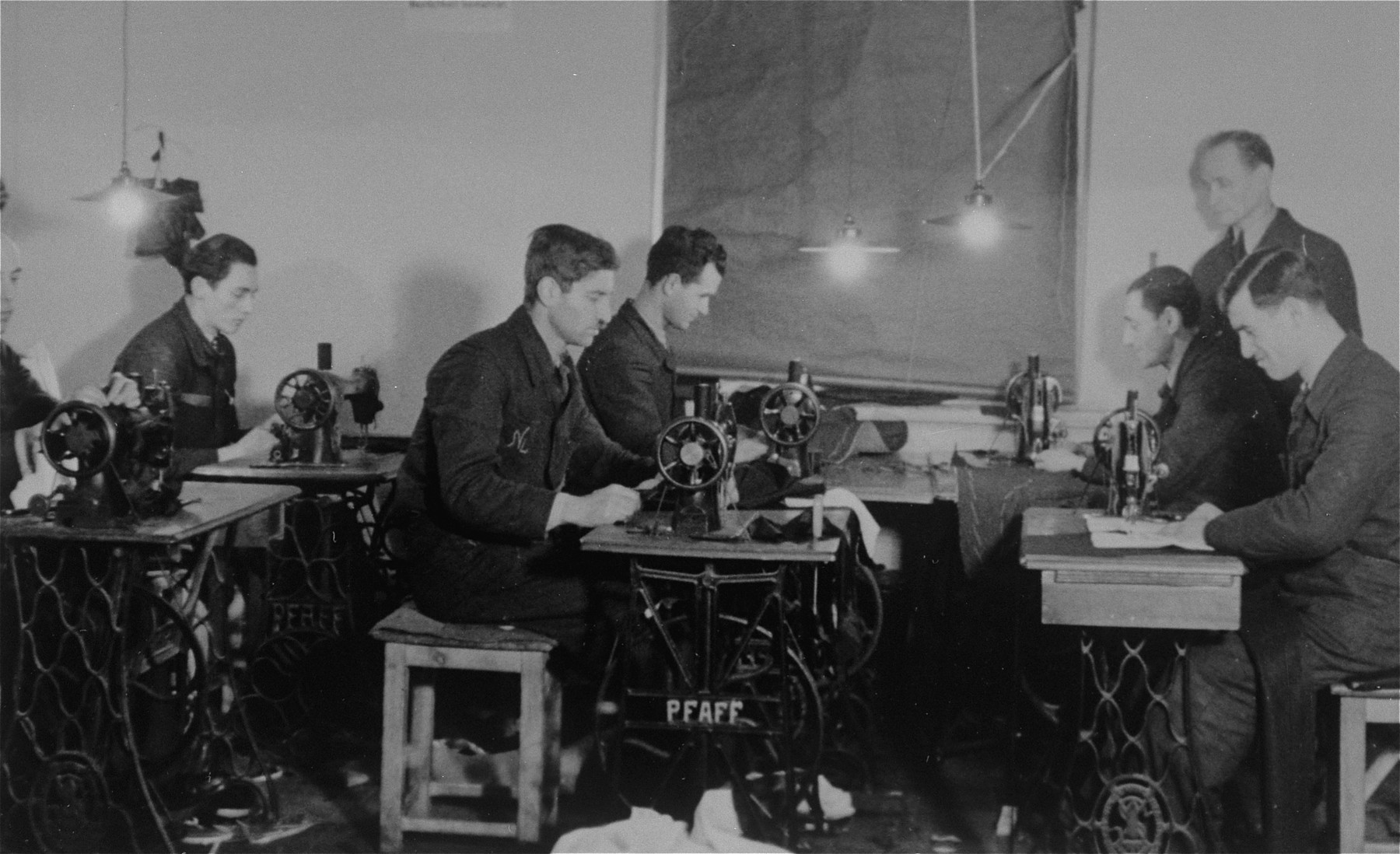 Jewish men work at sewing machines in a clothing workshop in the Bochnia ghetto.