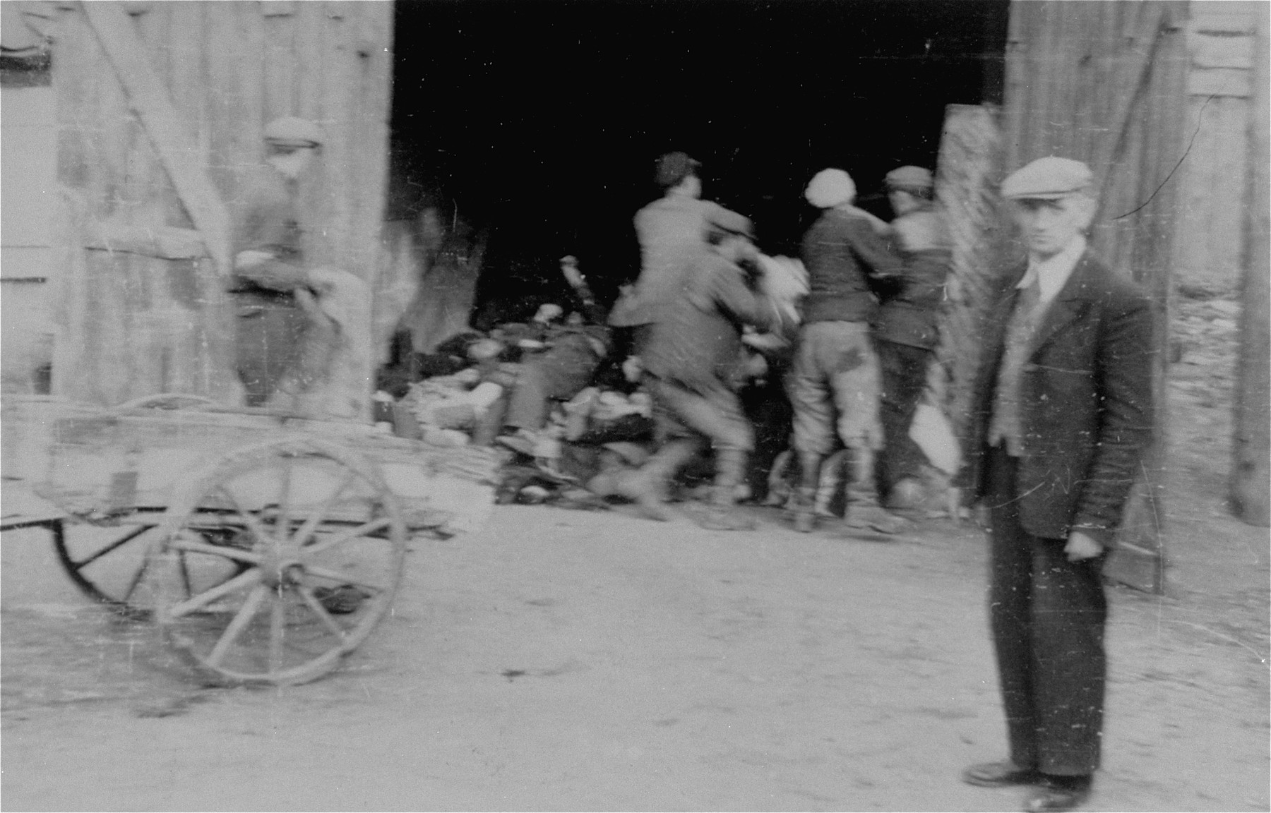 A Jewish council official named Kaminski (in the foreground) watches as men remove corpses from a cart and pile them in a barn in the Deblin Irena ghetto.