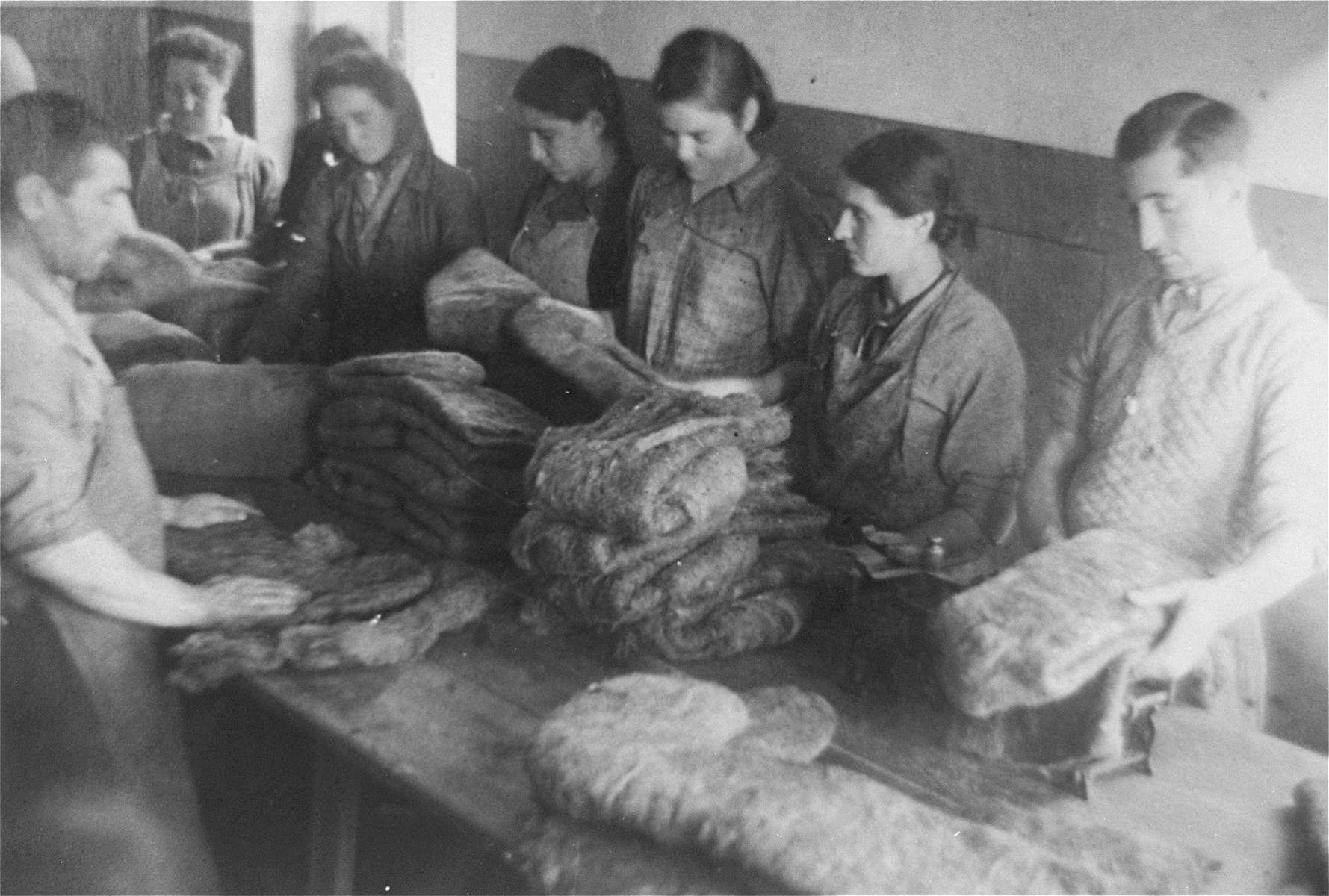 Jewish men and women make felt boots in a workshop in the Glubokoye ghetto.