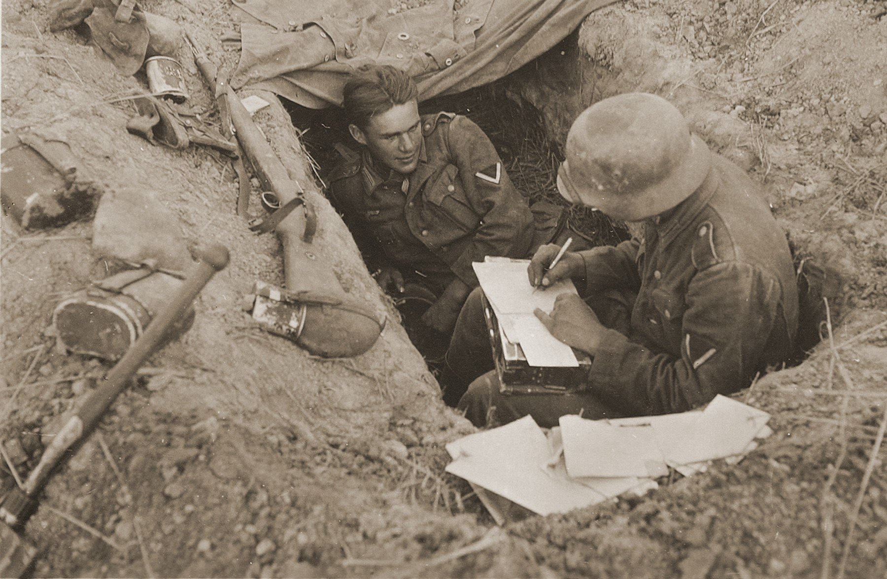 Two corporals in the German army rest in a foxhole during a lull in the fighting on the Eastern Front.  The man at right is writing either a letter or a report.