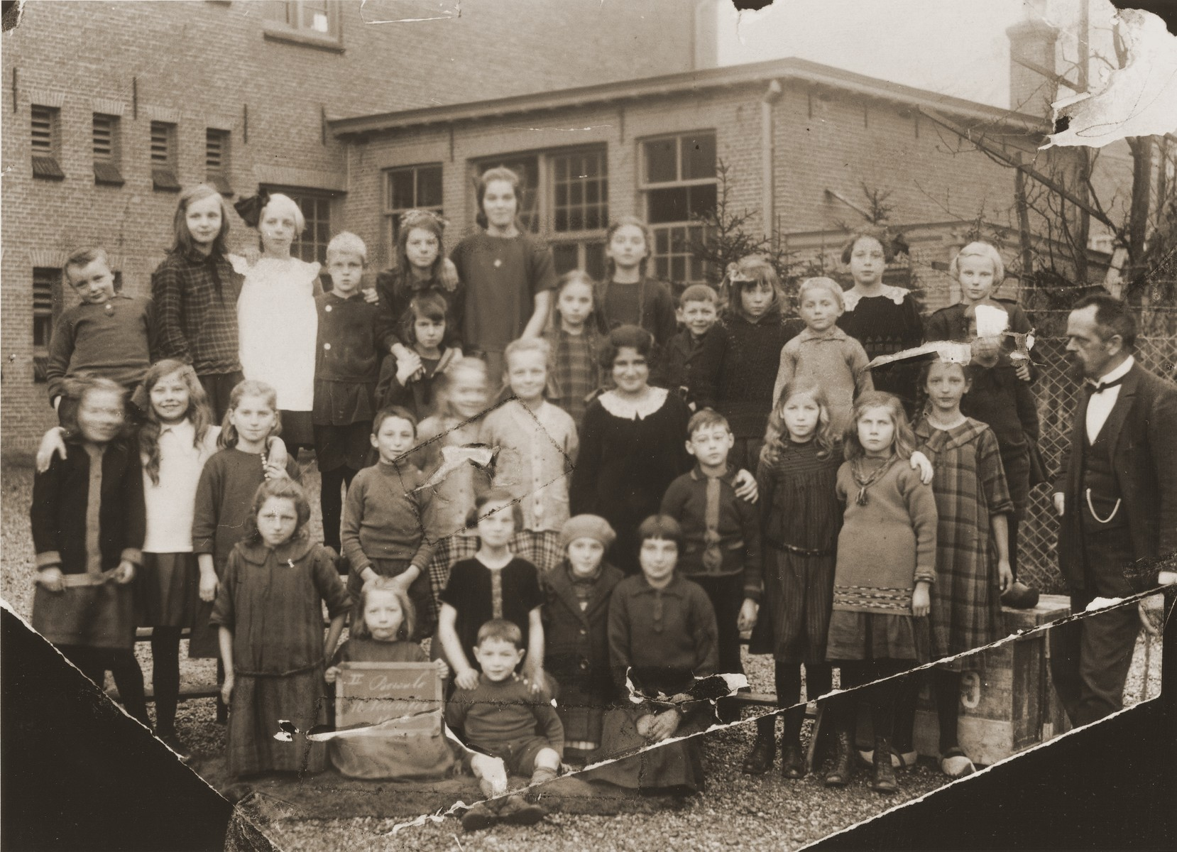 Group portrait of Dutch pupils at a public elementary school in Boekelo.  Among those pictured are: Michel Meijer (back row, fourth from the right, the short boy with bangs) Lou Slosser (second row from the front, third from the right); Richard Meijer (second row from the front, fourth from the left); Izak Meijer (little boy in front); Bettie Meijer (behind Izak); Bep Meijer (front row, wearing a beret); Renee (Sara) Meijer (front row, right side).