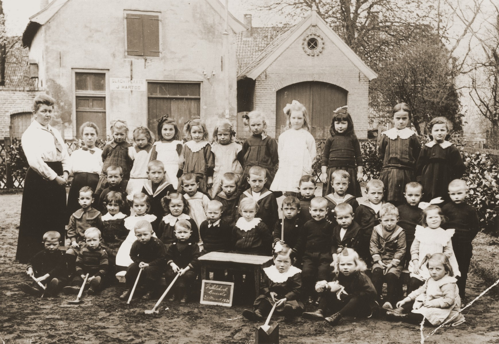 Class portrait of Dutch preschoolers, taken in front of the slaughterhouse owned by the Dutch Jew, Joseph Hartog.  Among those pictured are: Renee (Sara) Meijer (back row, fifth from the left) and Bettie Meijer (second row from the front, first on the right).