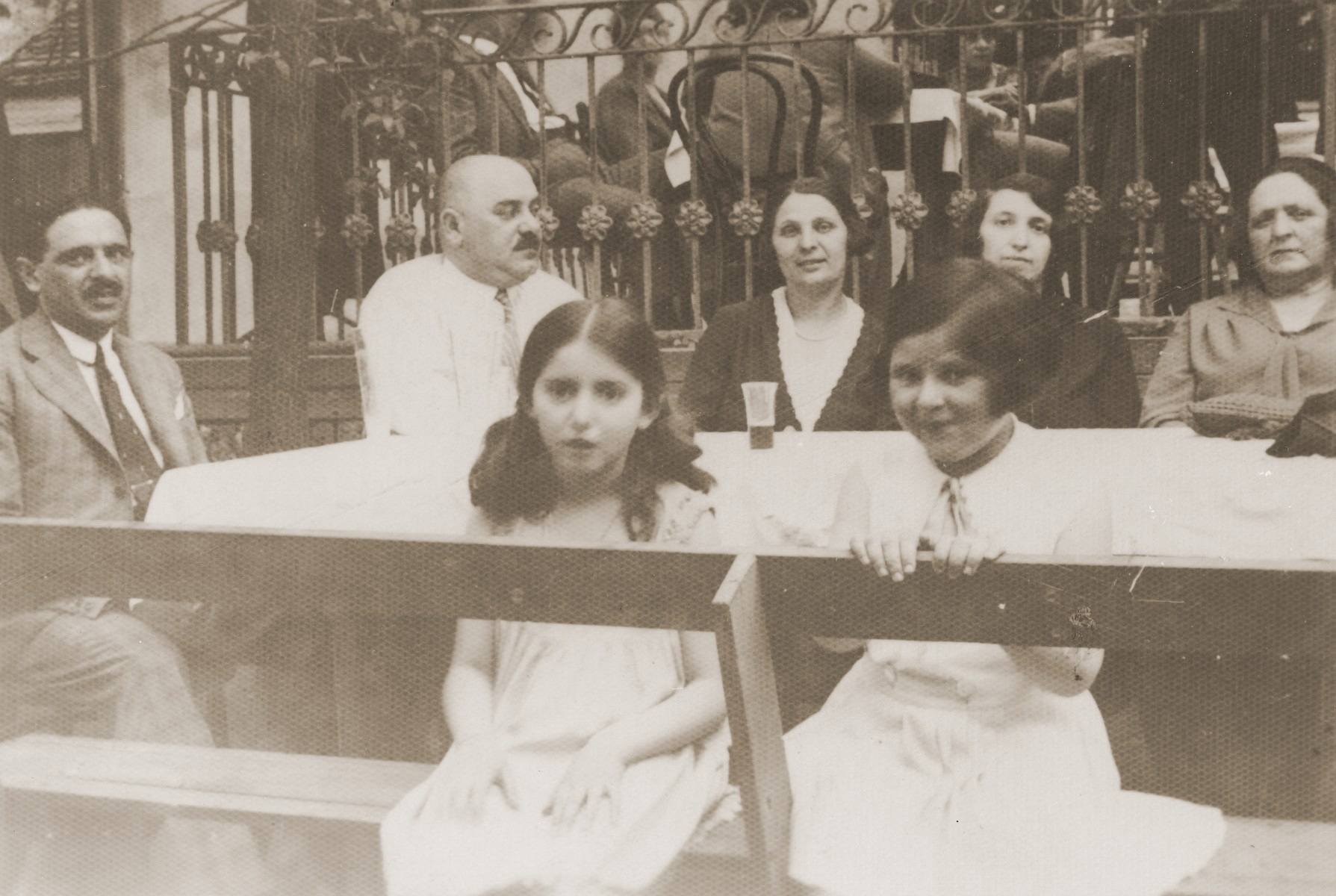 The Krausz and Winter families at an outdoor cafe in Budapest.  Among those pictured are Abraham Krausz (far left); Margit Krausz (center with glass); Auguszta Winter (mother of Margit, far right); and Klara Krausz (child at right).