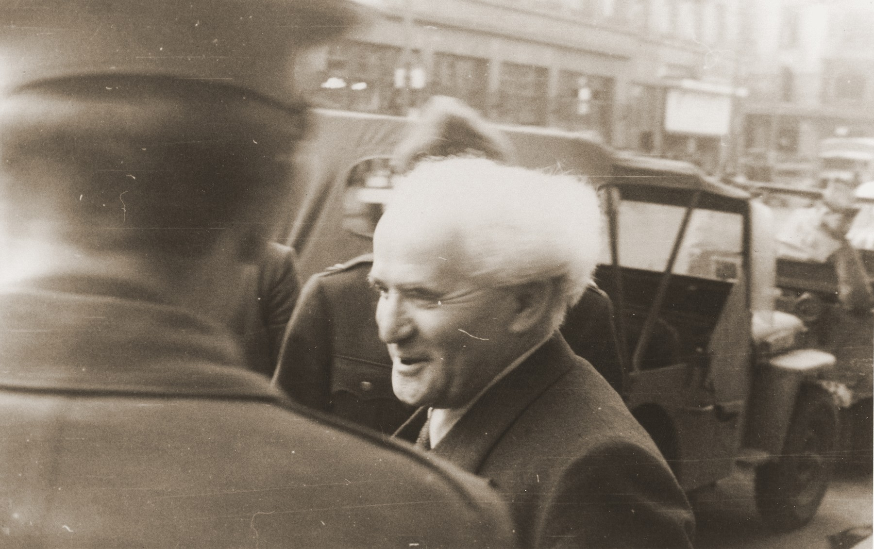David Ben-Gurion is greeted by Chaim Hoffmann (with his back to the camera) and others during an official visit to the American zone of Germany.    Ben-Gurion is on his way to the Babenhausen bei Aschaffenburg displaced persons camp near Frankfurt.