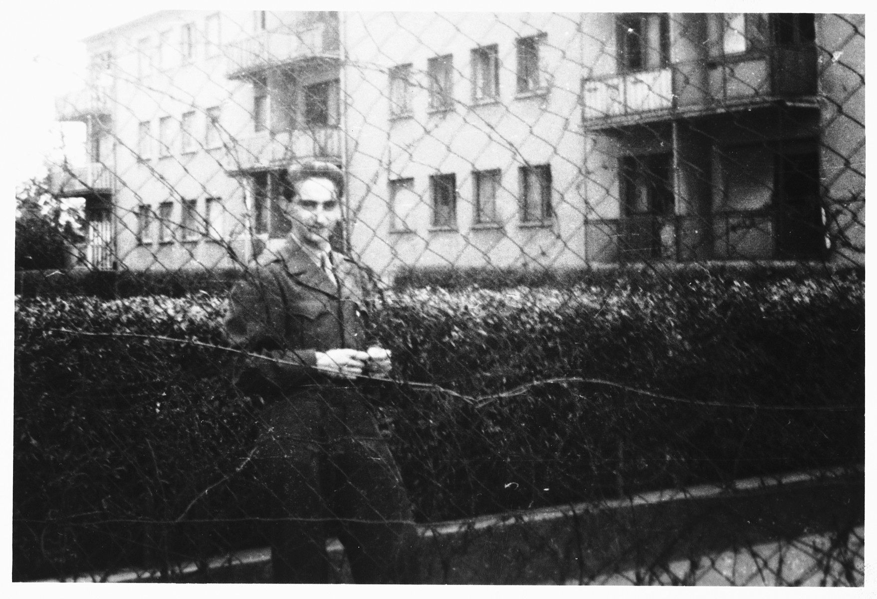 Shmuel Shalkovsky stands by a wire fence in his American army uniform while waiting to escort a group of DPs to America on board the Marine Perch.