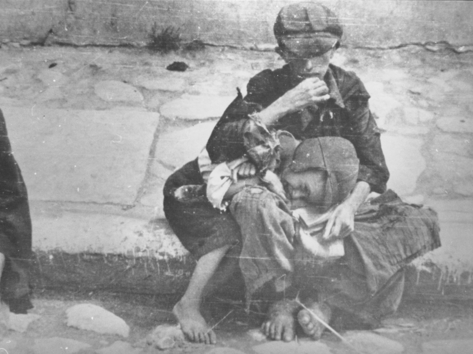 Destitute children sit barefoot on the pavement in the Warsaw ghetto.