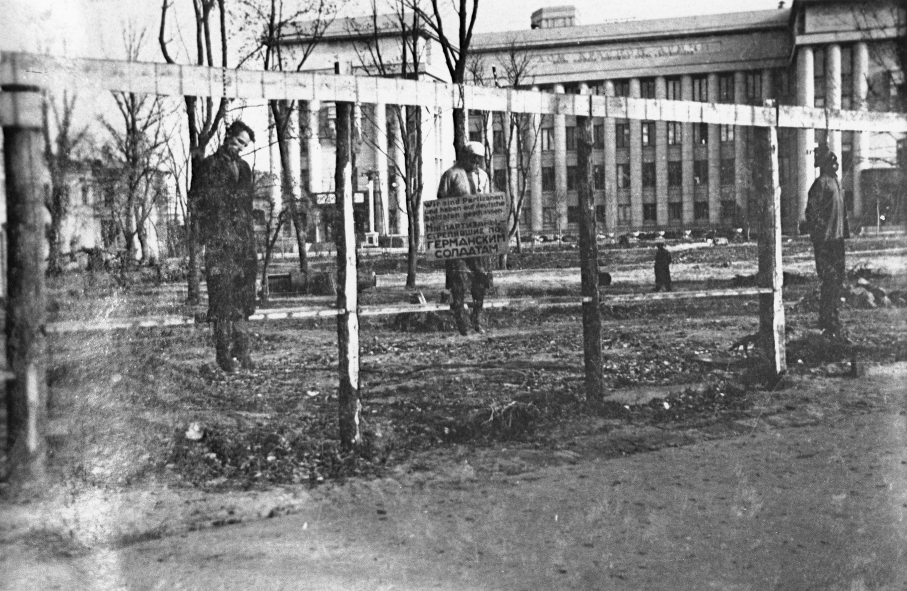 "The public hanging of three members of the Communist underground on Karl Marx Street in Minsk.  One of the victims wears a large placard around his neck that reads ""We are partisans and have shot at German soldiers.""  This execution was one of four carried out in Minsk on 26 October 1941 by German troops with the 707th Infantry Division.  Altogether, twelve members of the Communist underground were publicly hanged in four groups of three near a yeast-making factory.  This is believed to be the first public execution after the German invasion of the Soviet Union and it included the hanging of Masha Bruskina, a young Jewish woman.  In each of the four cases, the bodies were left to hang for several days to serve as a warning to would-be resisters."