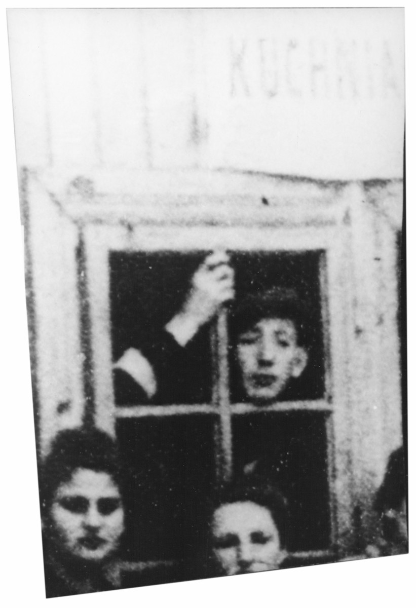 A Jewish youth peers out the window of a soup kitchen in the Cmielow ghetto.  Pictured at the window is Toivia Grunbaum (now Teddy Greenbaum).