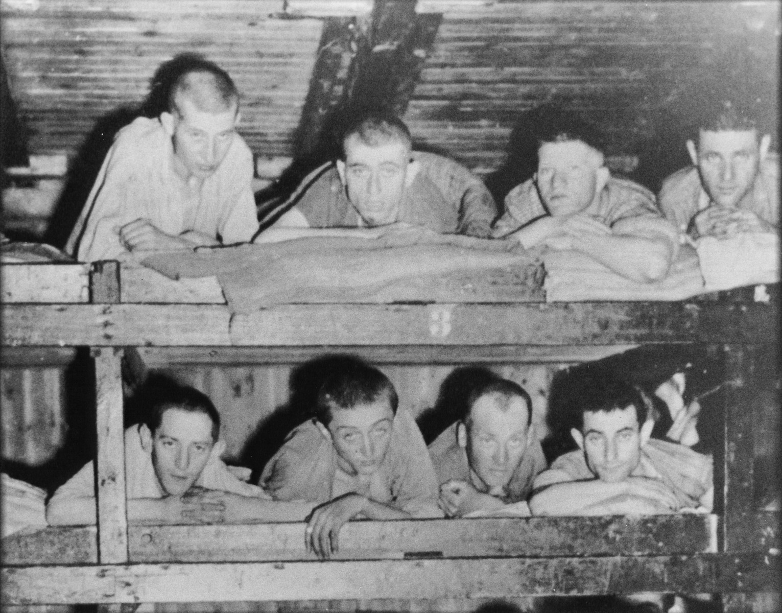 Survivors lie in the top two tiers of a wooden bunk in a barracks in the Buchenwald concentration camp.