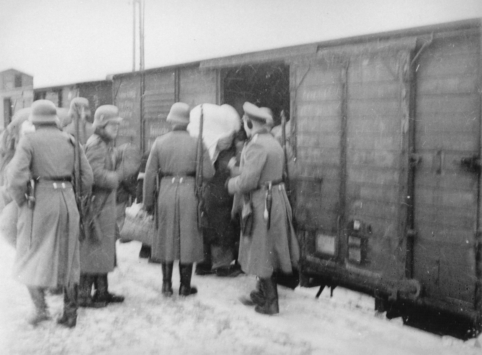German soldiers oversee the boarding of Jews from the Zyradow ghetto onto a deportation train.