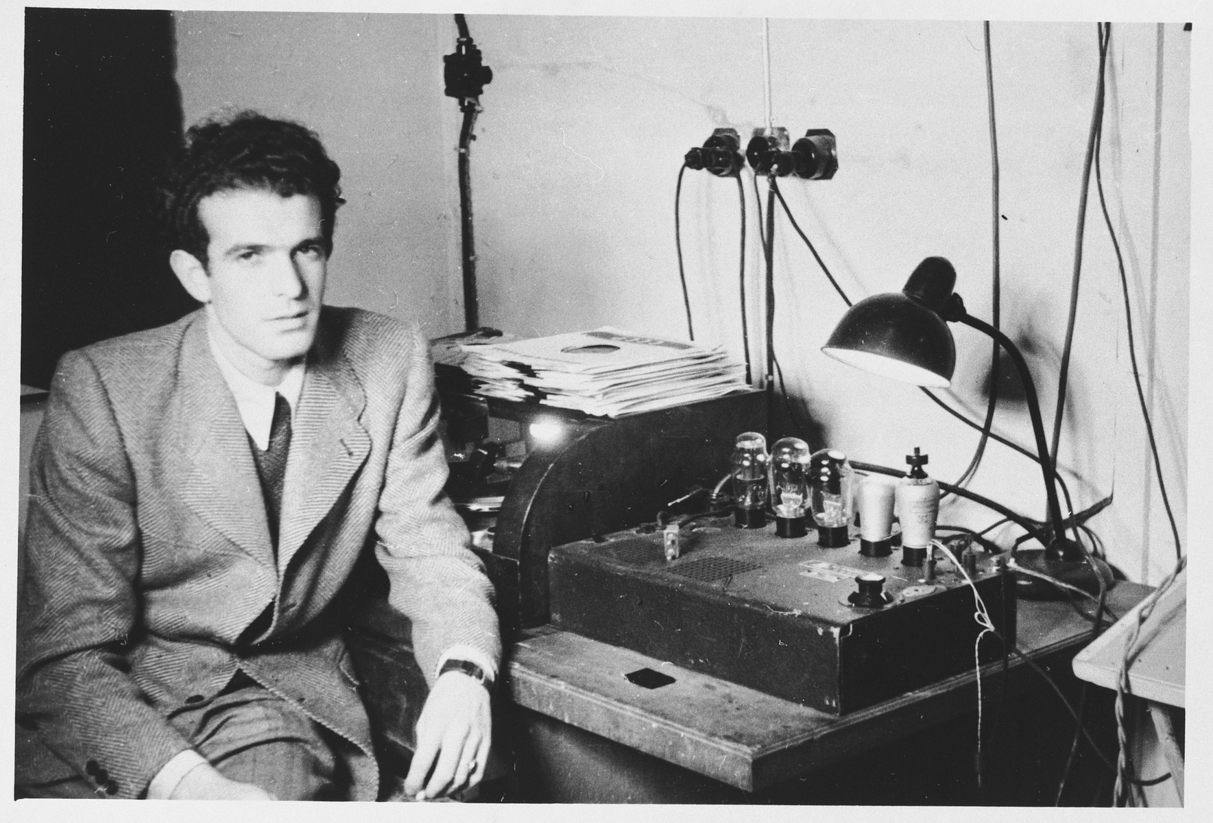 A Jewish DP radio broadcaster poses by his equipment and a stack of records in the Schlachtensee displaced persons camp.