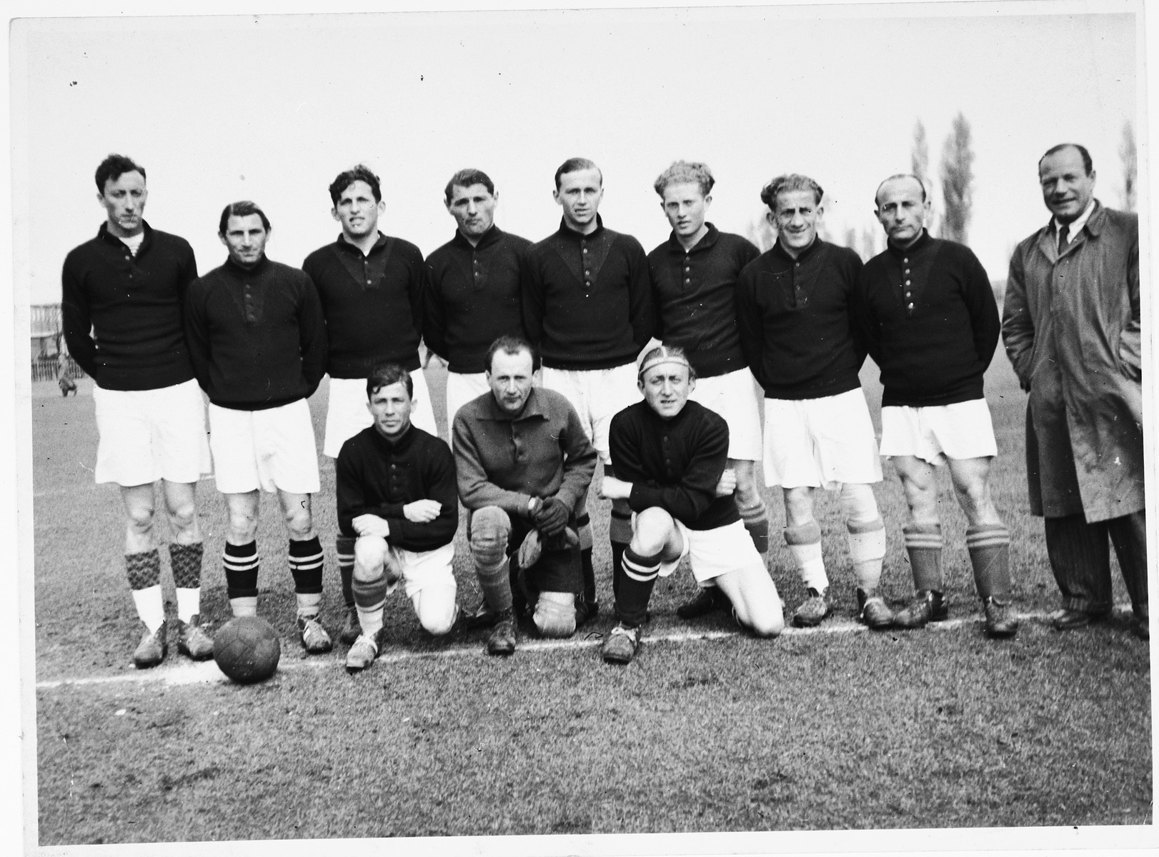 Group portrait of the members of the Schlachtensee displaced persons camp soccer team.  Among those pictured are Moritz Sachs (standing third from the left), Jacob (Yanek) Czarny (later Jack Charney, fourth from the left); and Simon Krumhloz (the manager, standing on the right in the coat and tie).