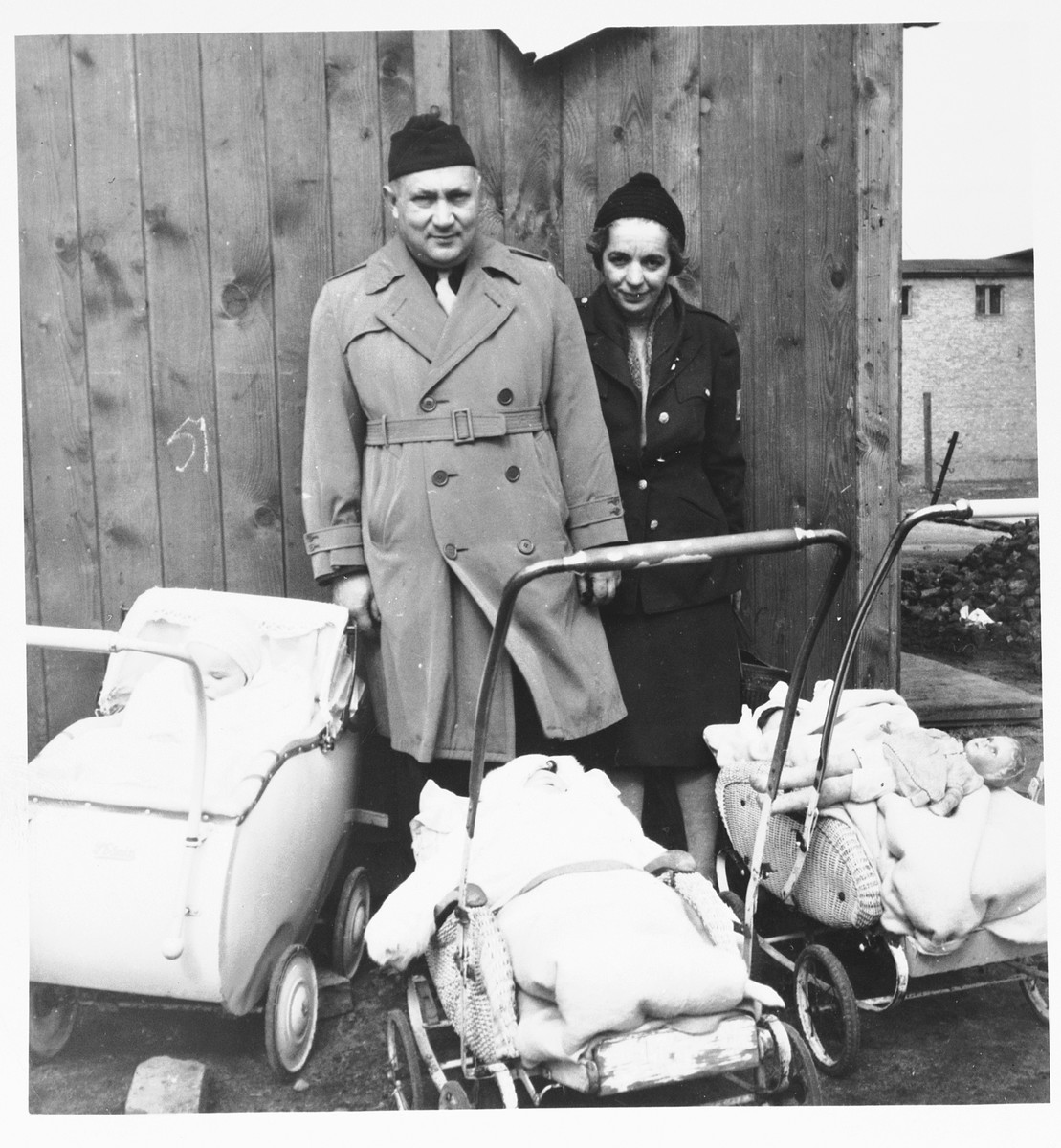 UNRRA camp director Harold Fishbein and an unidentified woman pose with three babies in carriages at the Schlachtensee displaced persons camp.