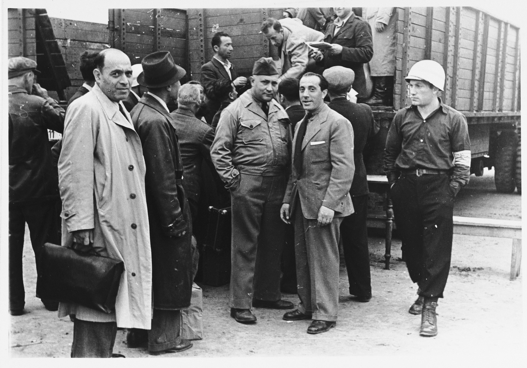 UNRRA camp director Harold Fishbein poses with other officials at the Schlachtensee displaced persons camp, where Jewish DPs are boarding large trucks.    Harold Fishbein is standing in the center (third from the right).