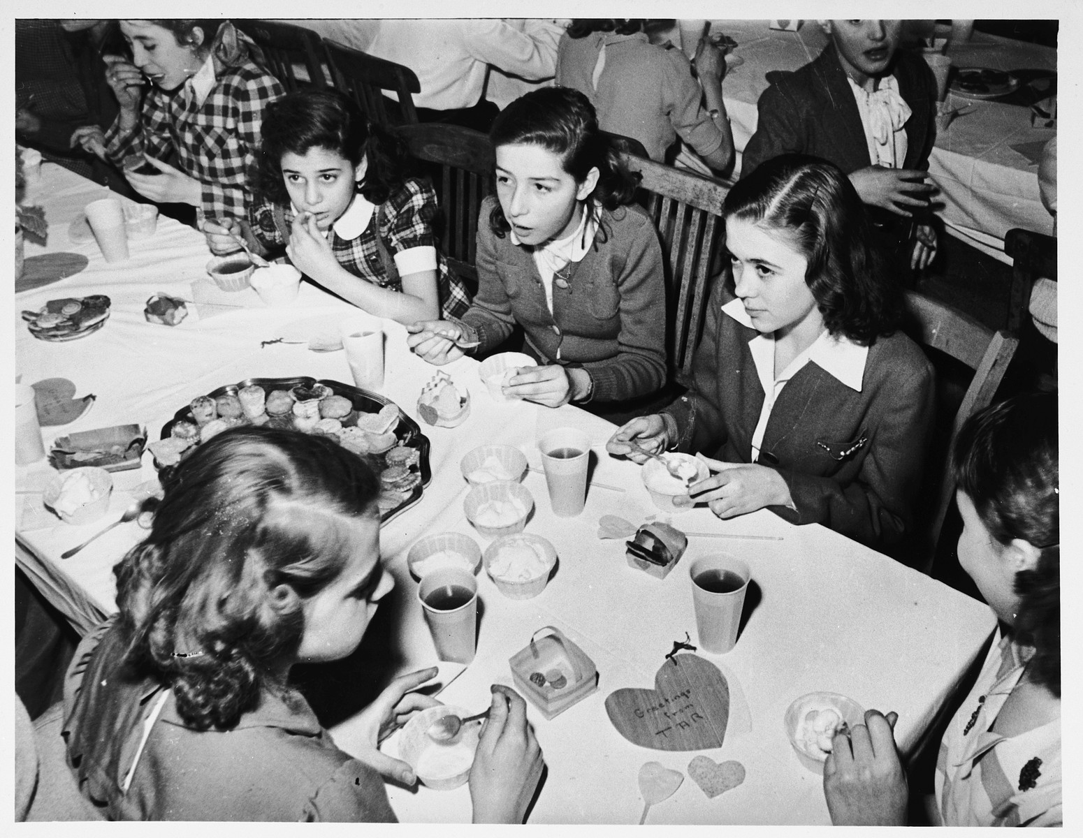 Jewish DP girls sit around a table eating ice cream at a party in the Schlachtensee displaced persons camp.