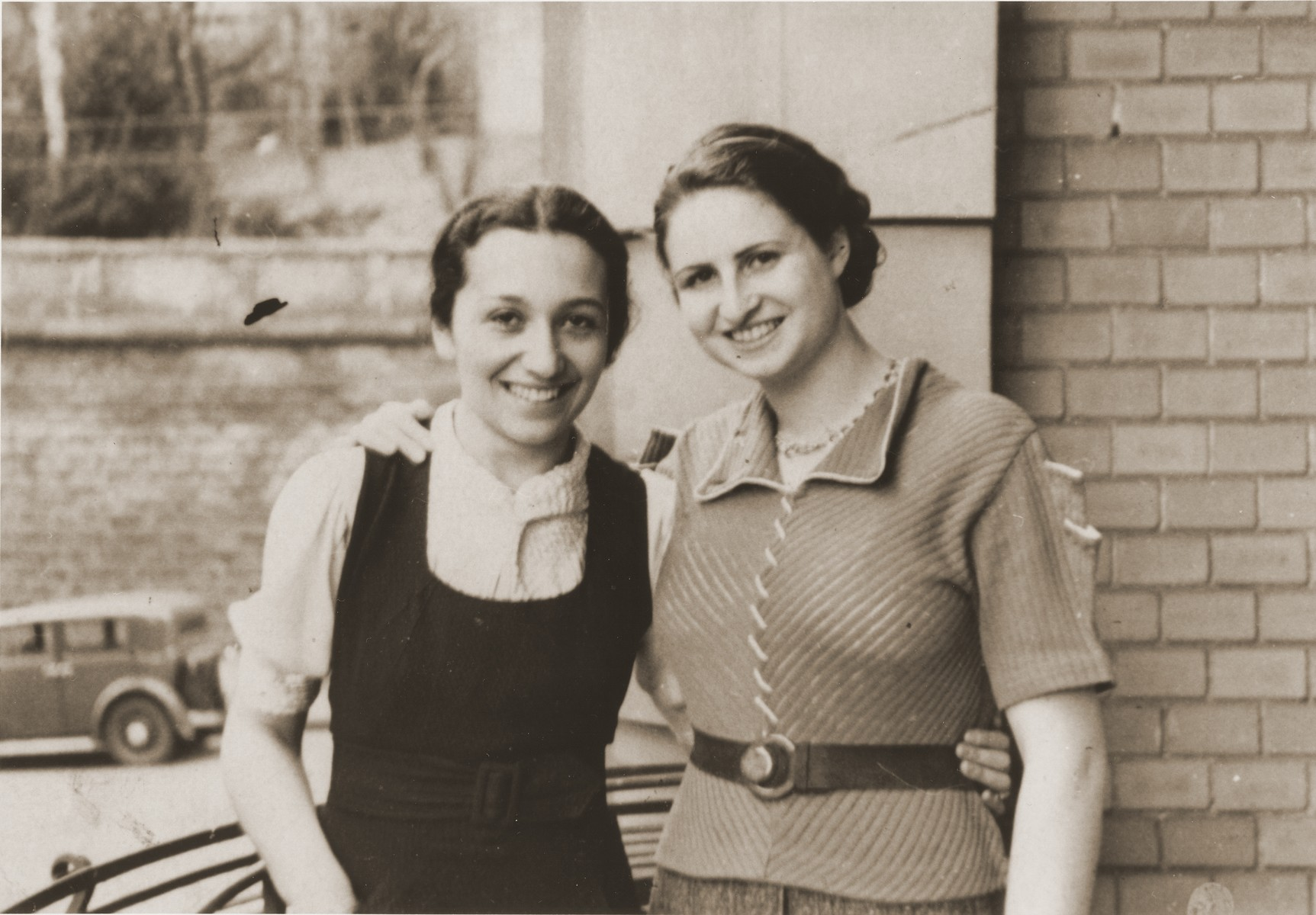 Two young Jewish women pose with their arms around each other in front of a house.