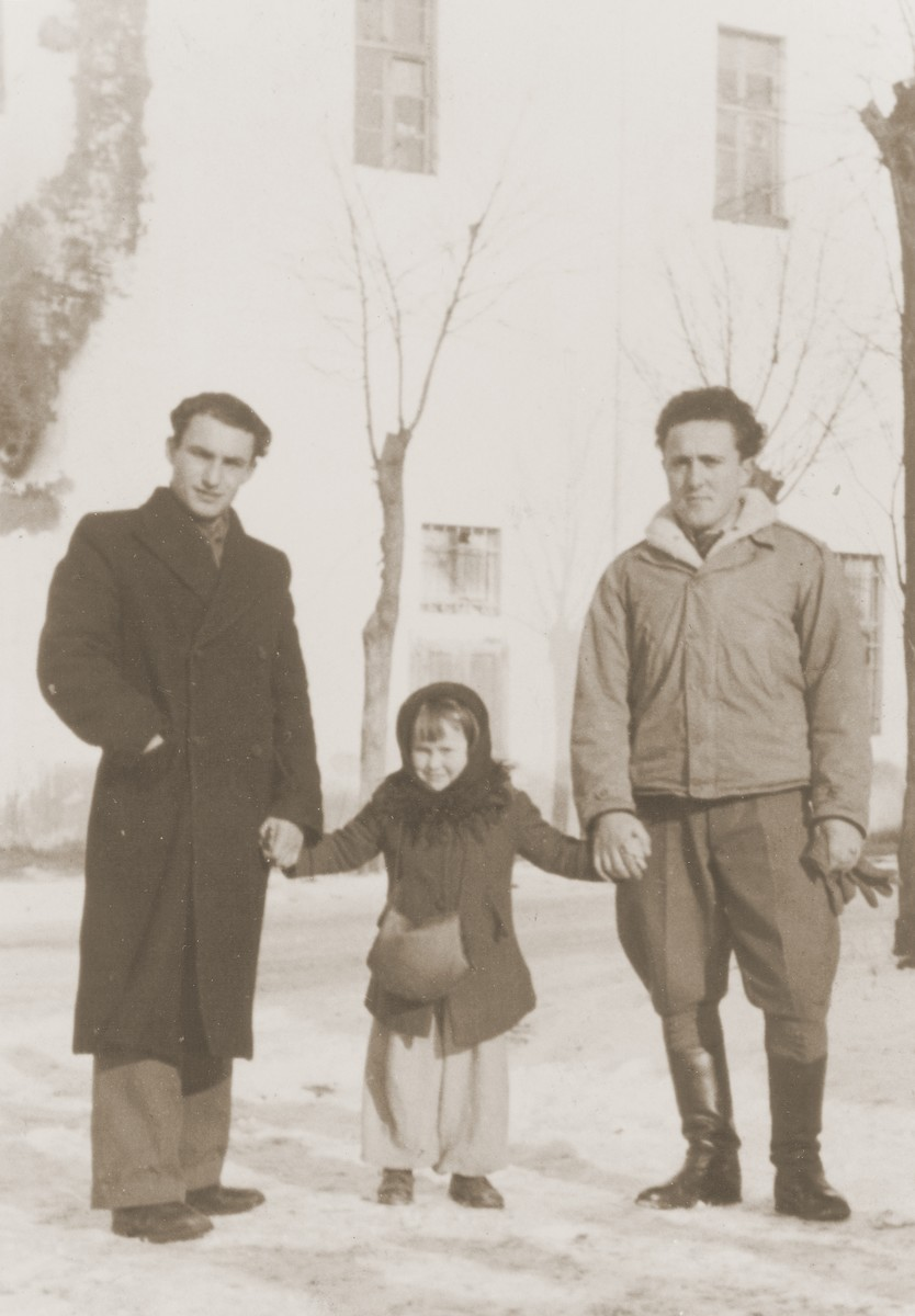 A Jewish DP child poses outside with two young men in the Cremona displaced persons camp.  Pictured is Masha Leikach.