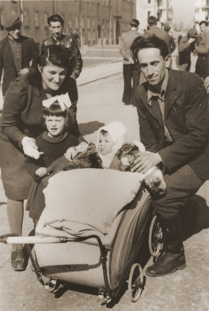 A Jewish DP family poses with a baby carriage on a street in Lodz after the war.    Pictured are Moshe and Riva Prager with their children Chele and Mina.