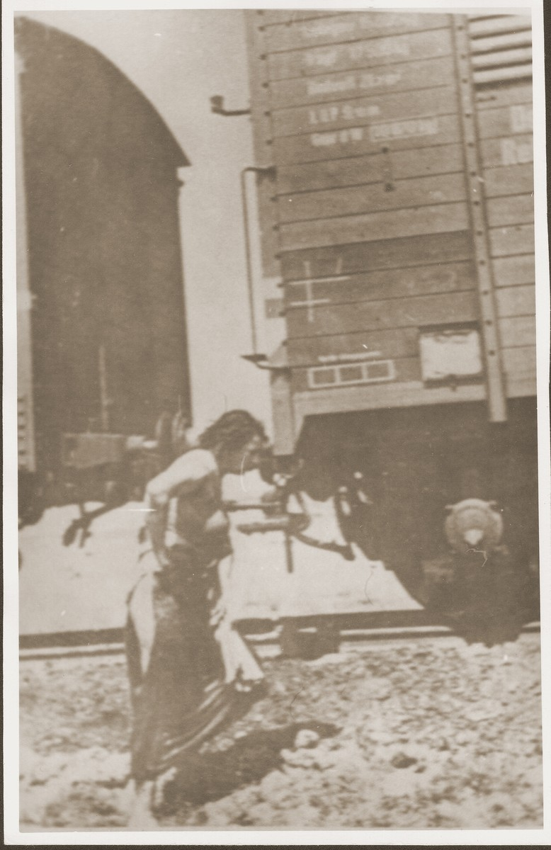 A partially clothed Jewish woman who is a passenger on the Iasi death train, walks beside the train during a stop on the journey.
