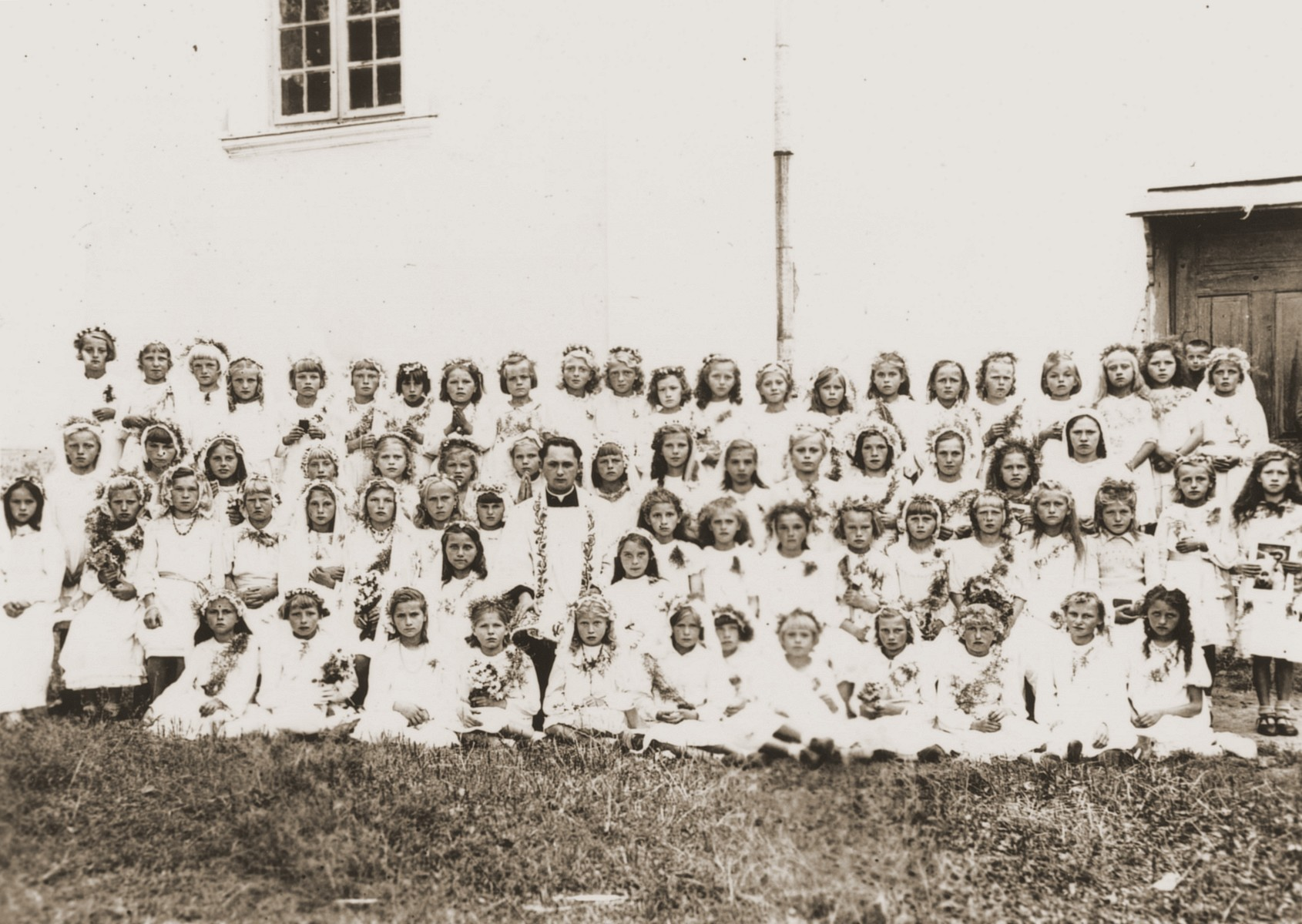 Group portrait of girls at a church school in Wysokie Mazowieckie, Poland, who are dressed for their first communion.  Among the children are twin Jewish sisters who are living in hiding.  The Jewish twins, Celina and Fela Friedmann, are pictured standing in the center of the back row.