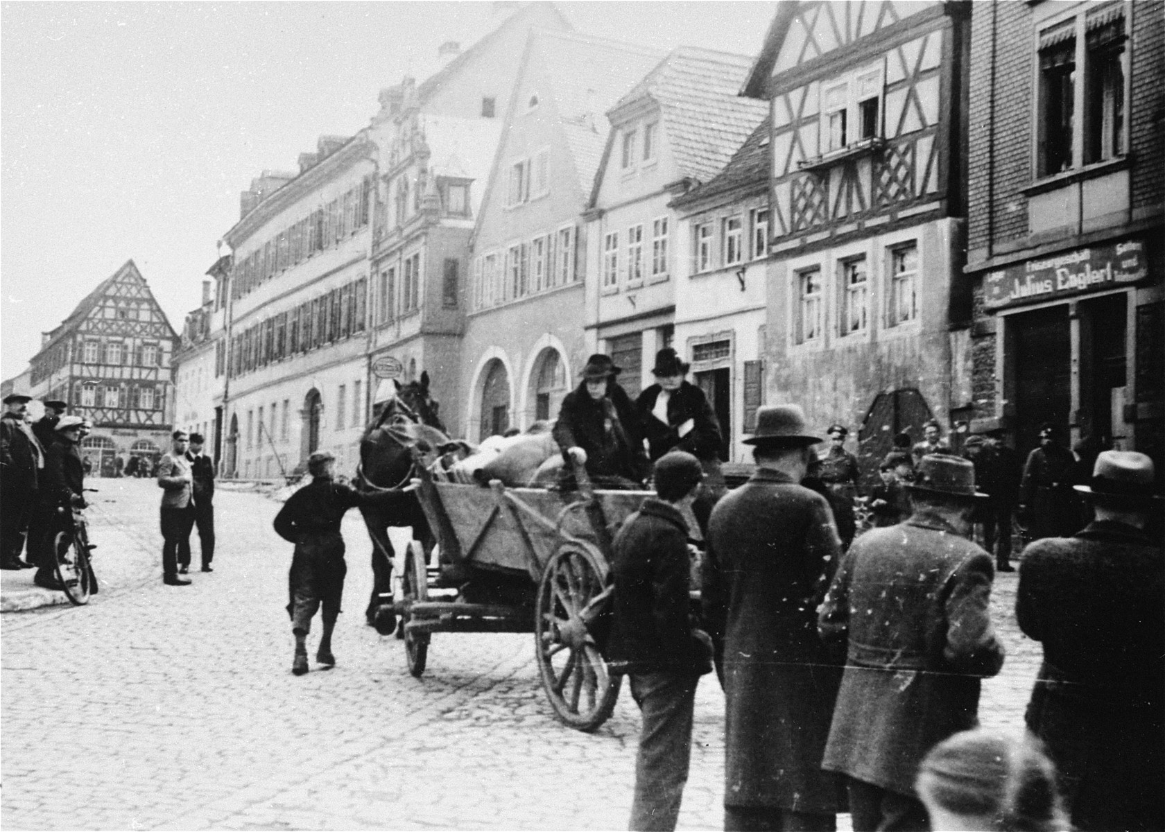 Two elderly Jewish women arrive at the Fränkischen Hof assembly center in a horse-drawn wagon during a deportation action in Kitzingen.