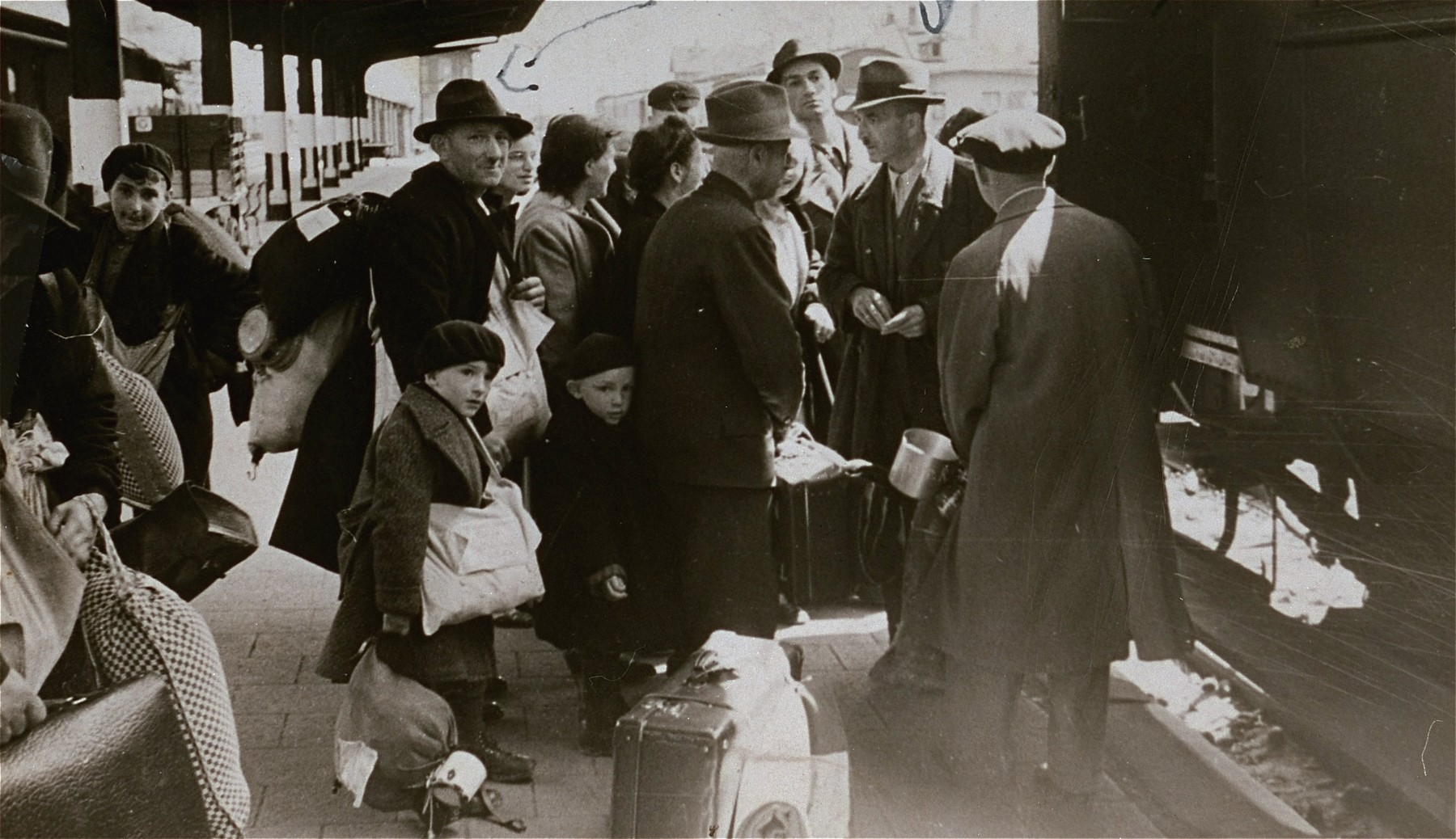 Jewish deportees from the Hanau, Gelnhausen and Schluechtern districts board the deportation train at the Hanau station.  Among those pictured is Kurt Levi (age 13, at the far left) from Ostheim, and Ludwig Gernsheimer from Rueckingen (in the middle) with his two sons, Hans (age 6) and Lothar (age 4). Gernsheimer was the chairman of the Jewish community of Rueckingen and was the donor's uncle.  He and his children perished.